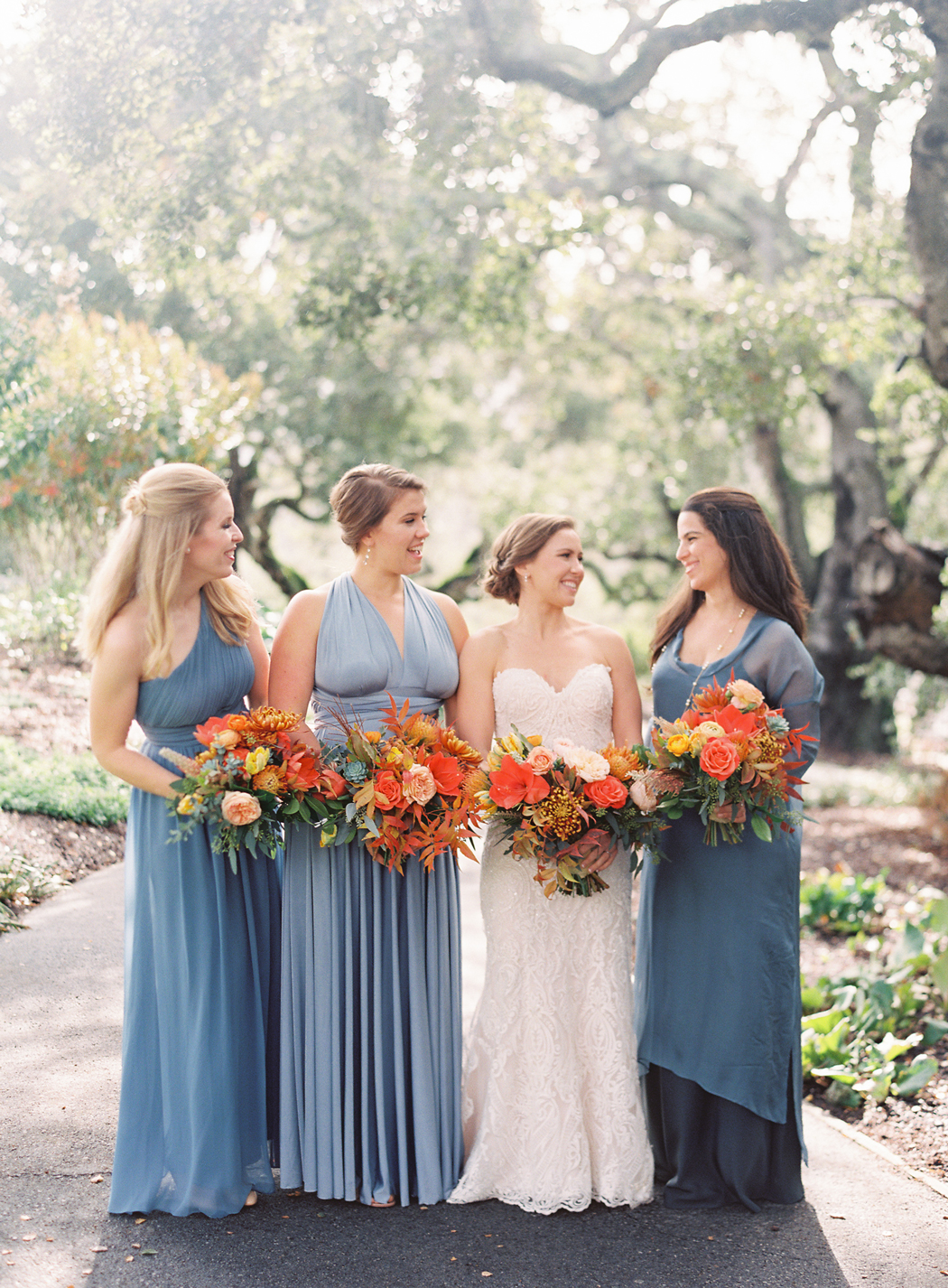 bride with bridesmaids wearing various blue shade dresses