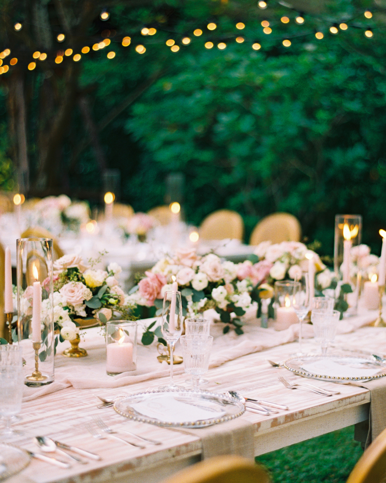 latte colored table runners under low floral centerpieces and taper candles