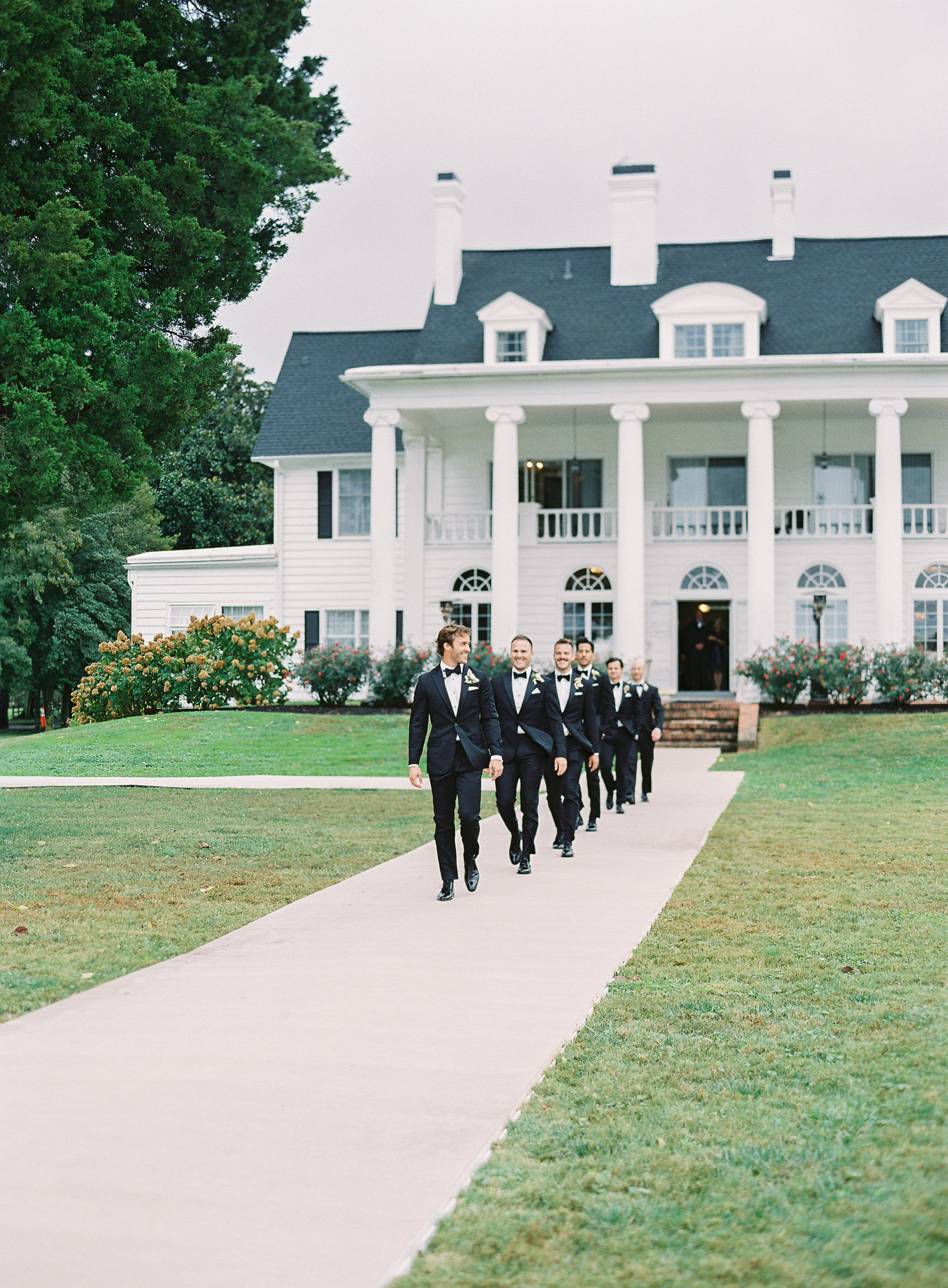 lauren alex wedding groomsmen walking in front of manor