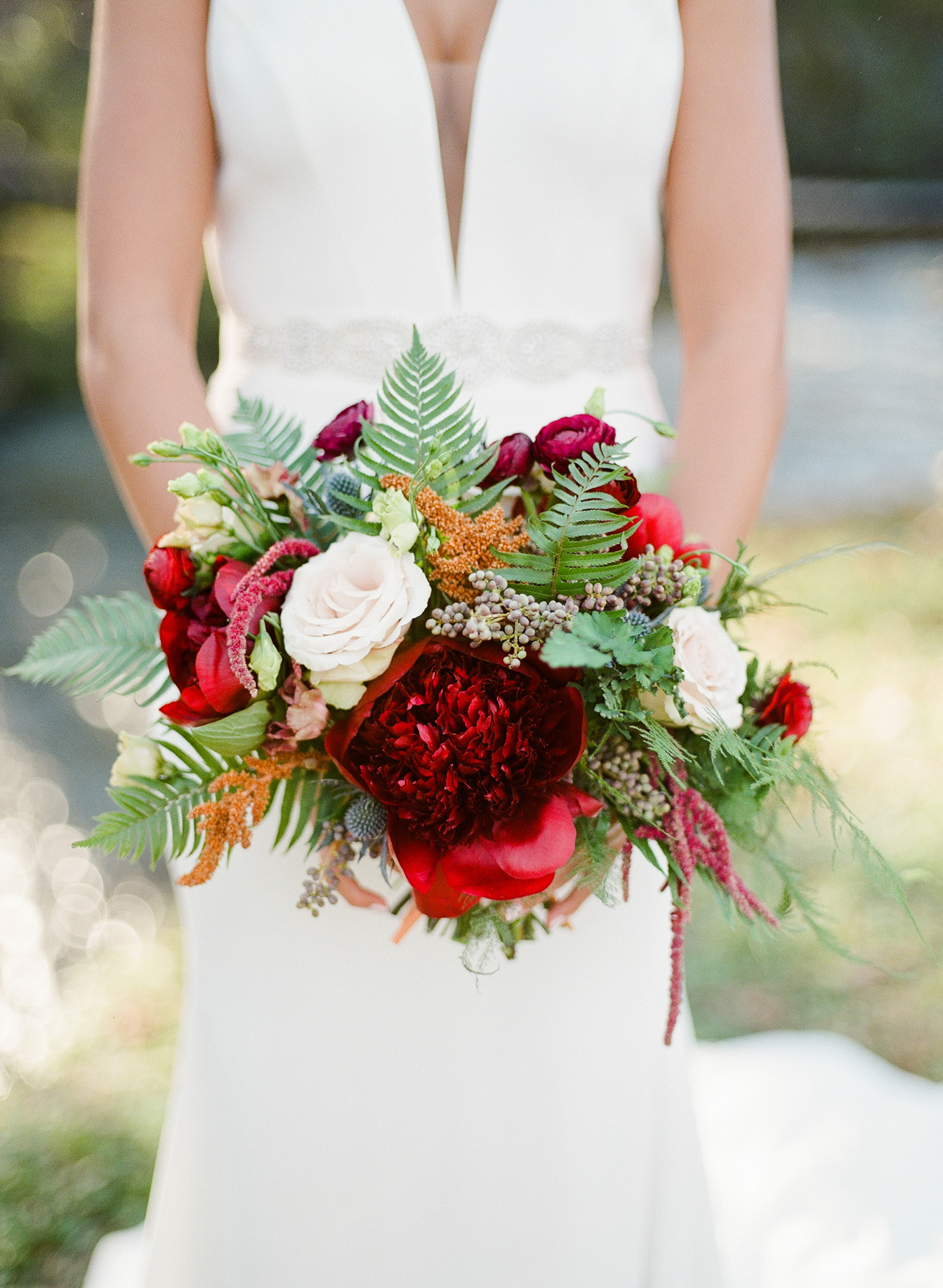 burgundy ranunculous and peonies, quicksand roses, deep blue privet berry, and bronze amaranthus with leafy ferns bouquet