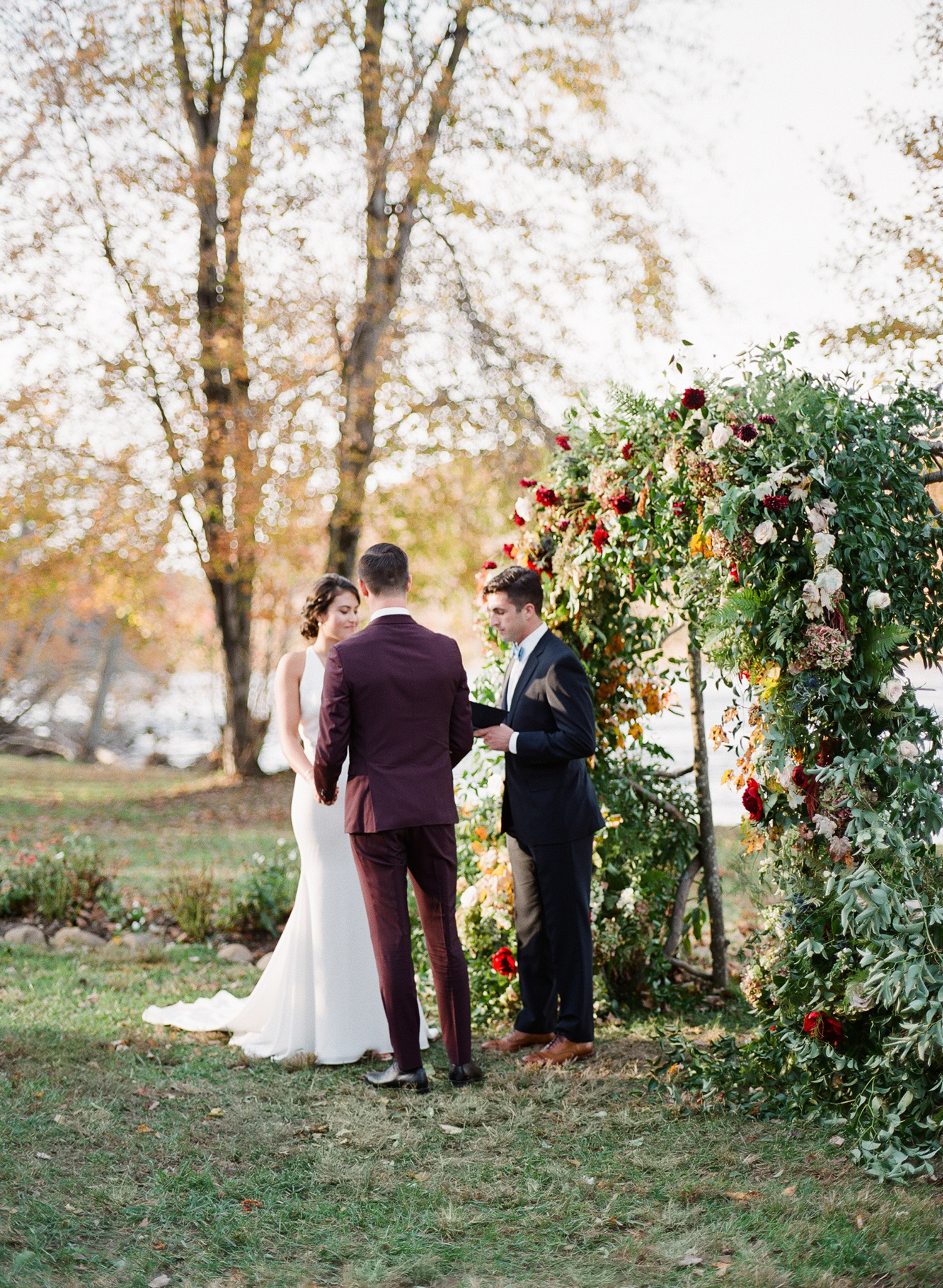 floral arch wedding ceremony backdrop by bride and groom