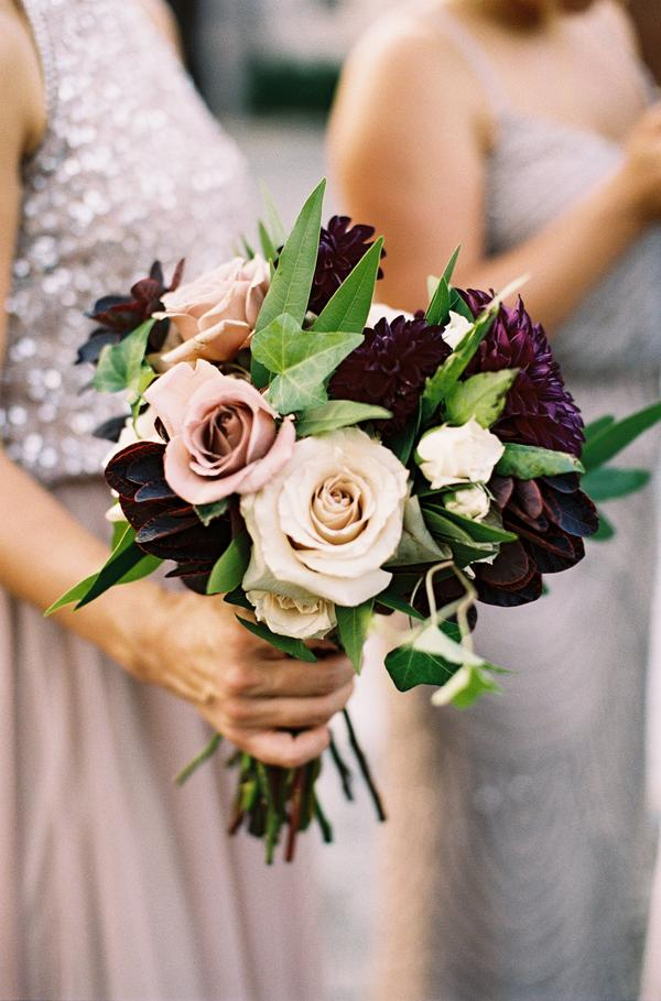 bridesmaid holding blush roses and dark purple dahlia bouquet
