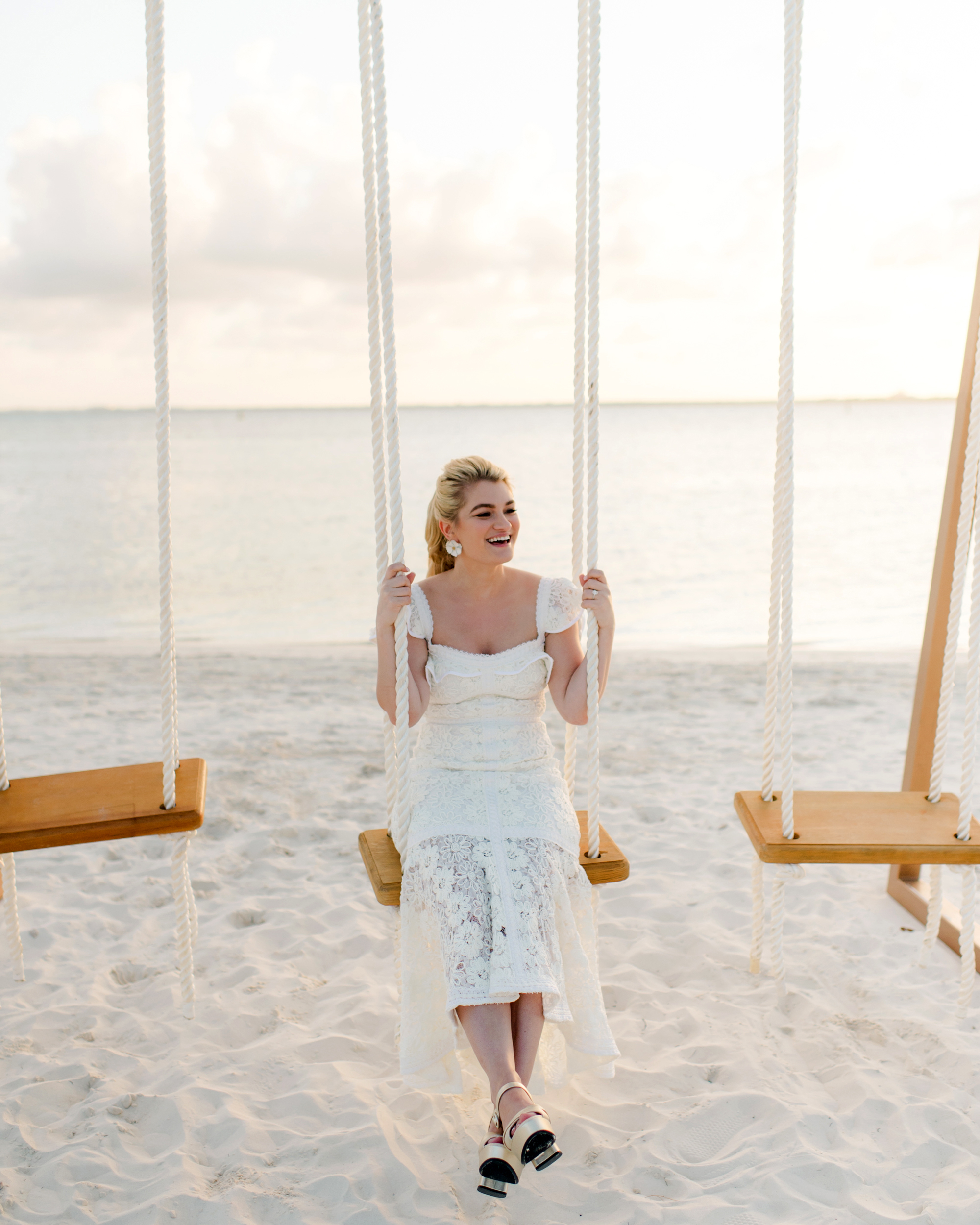 bride sitting on wood and rope swing set on beach