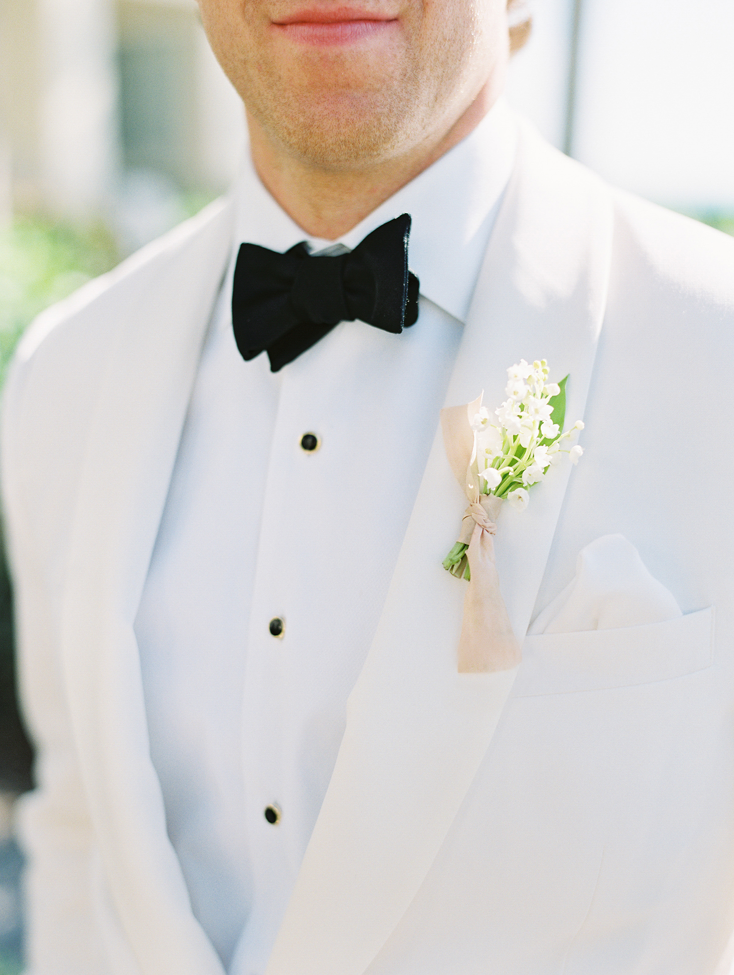 beth john wedding boutonniere on white suit