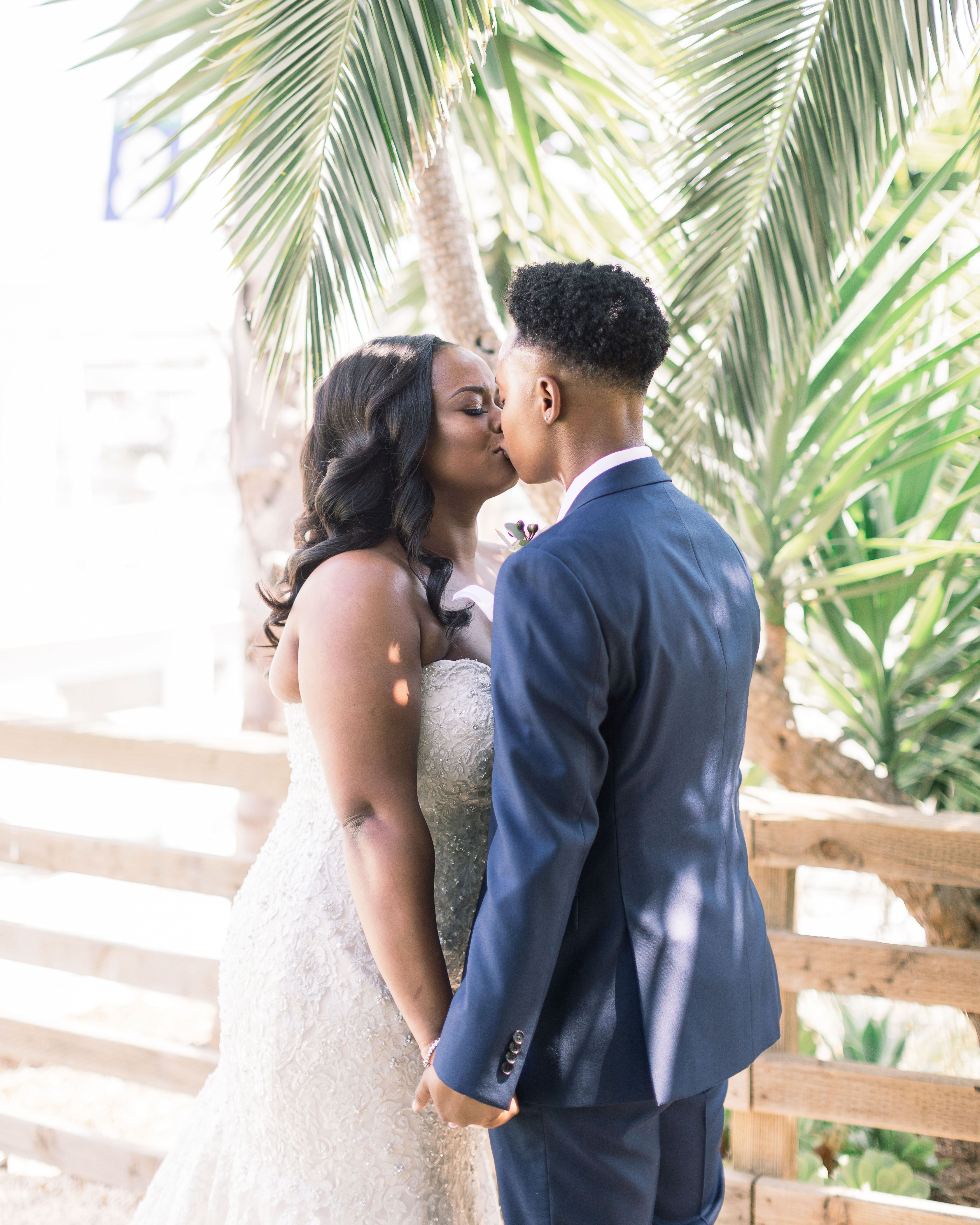 outdoor wedding kiss under tropical tree