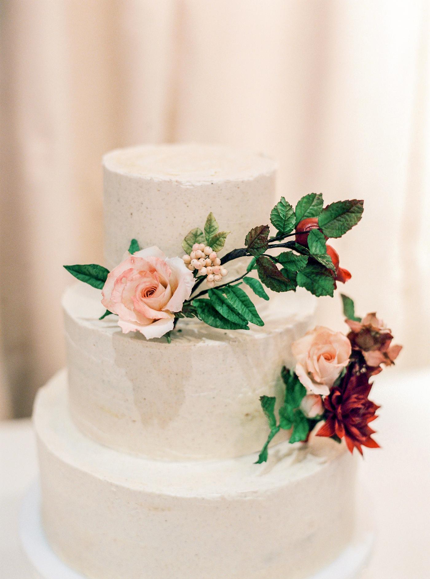 spiced vanilla bean buttercream iced three tier wedding cake with floral decor