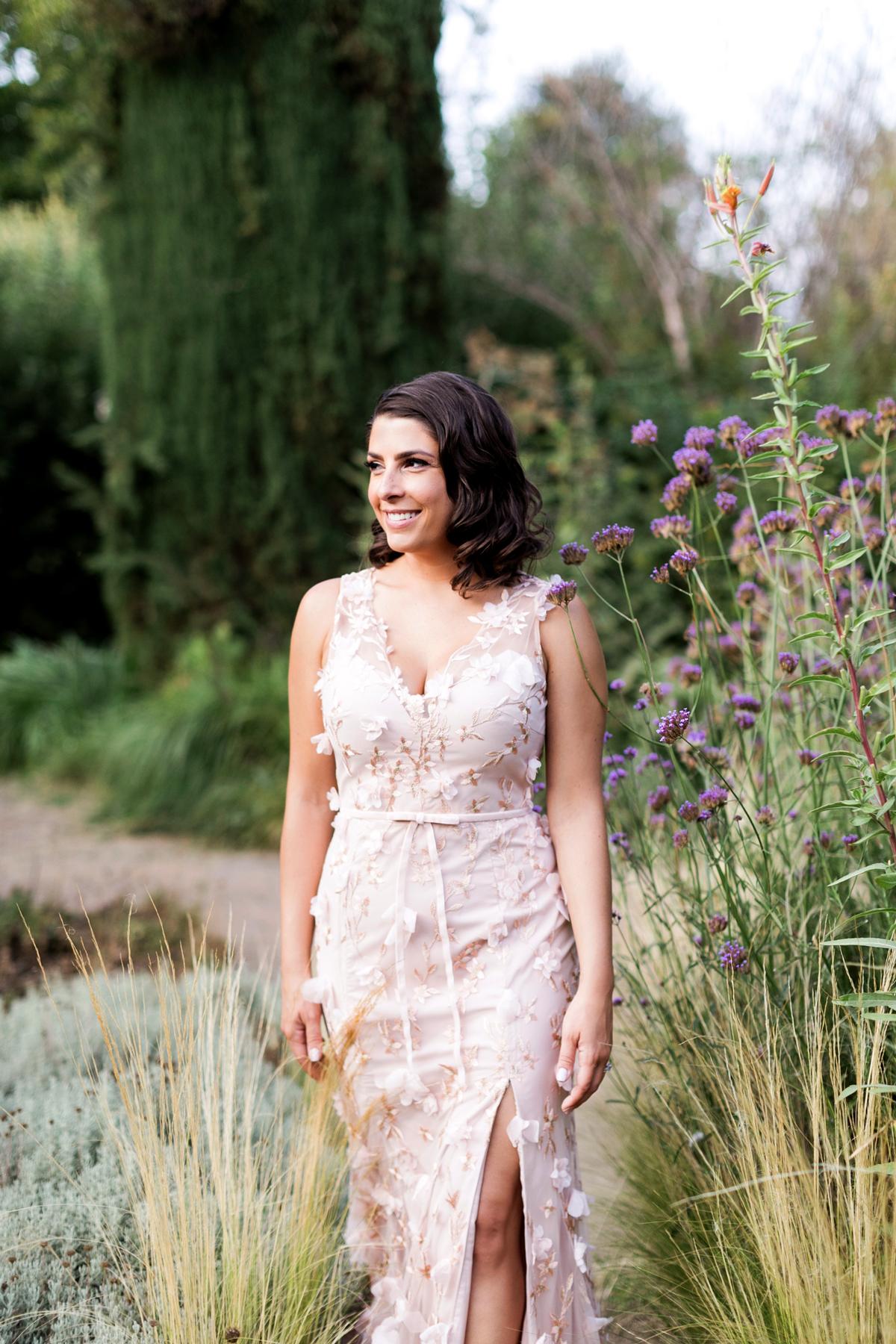 bride wearing blush-colored, 3D floral appliquéd, sleeveless, side-slit, think bow belt, floor length gown