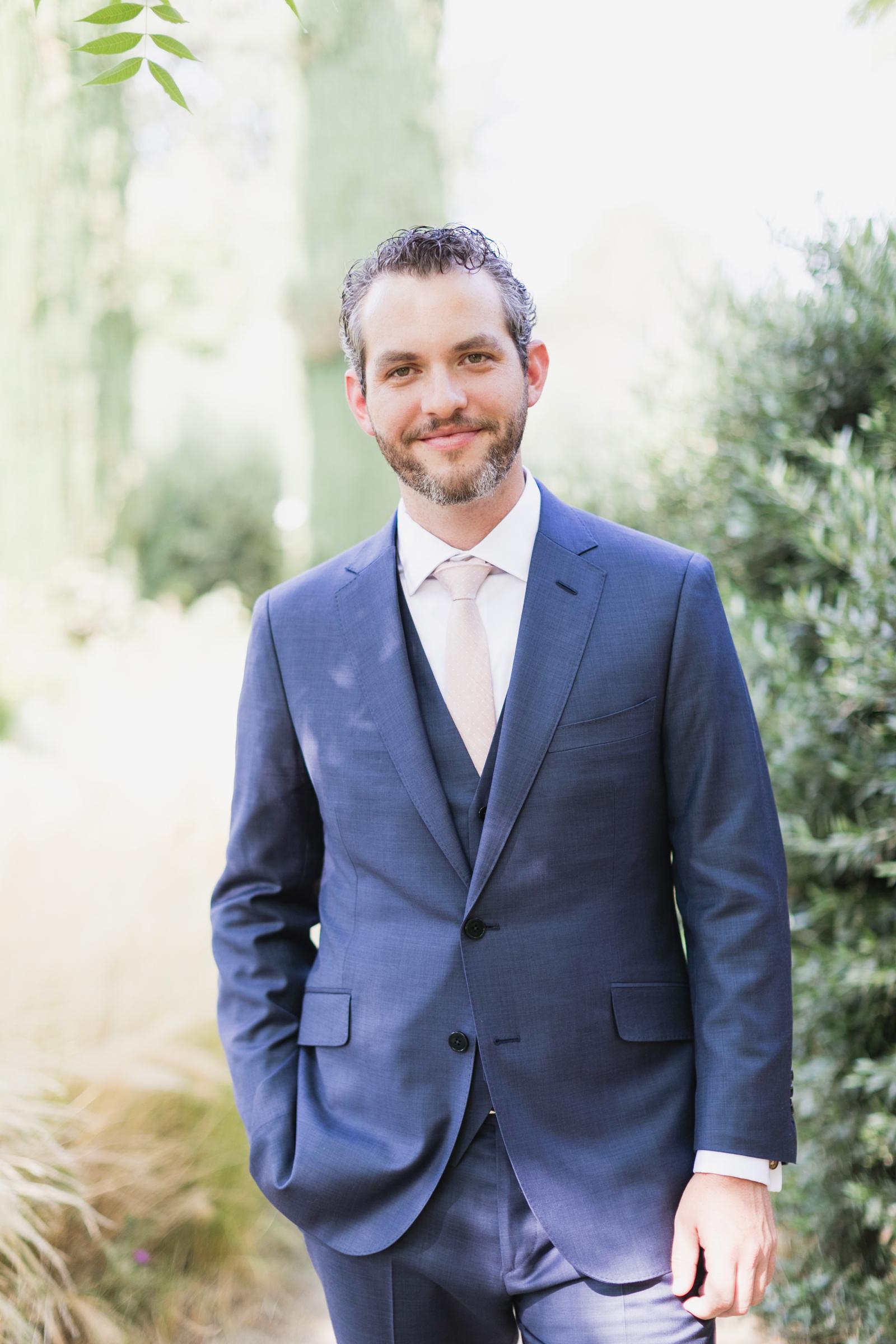 blue custom three-piece Trumaker suit with cream colored tie