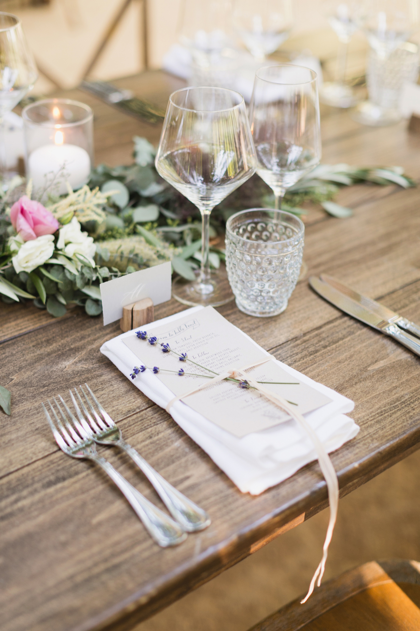 menus tied with string and lavender sprigs on wooden table