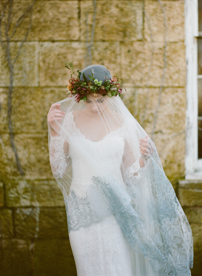 bride wearing veil with gray lace edges and flower crown
