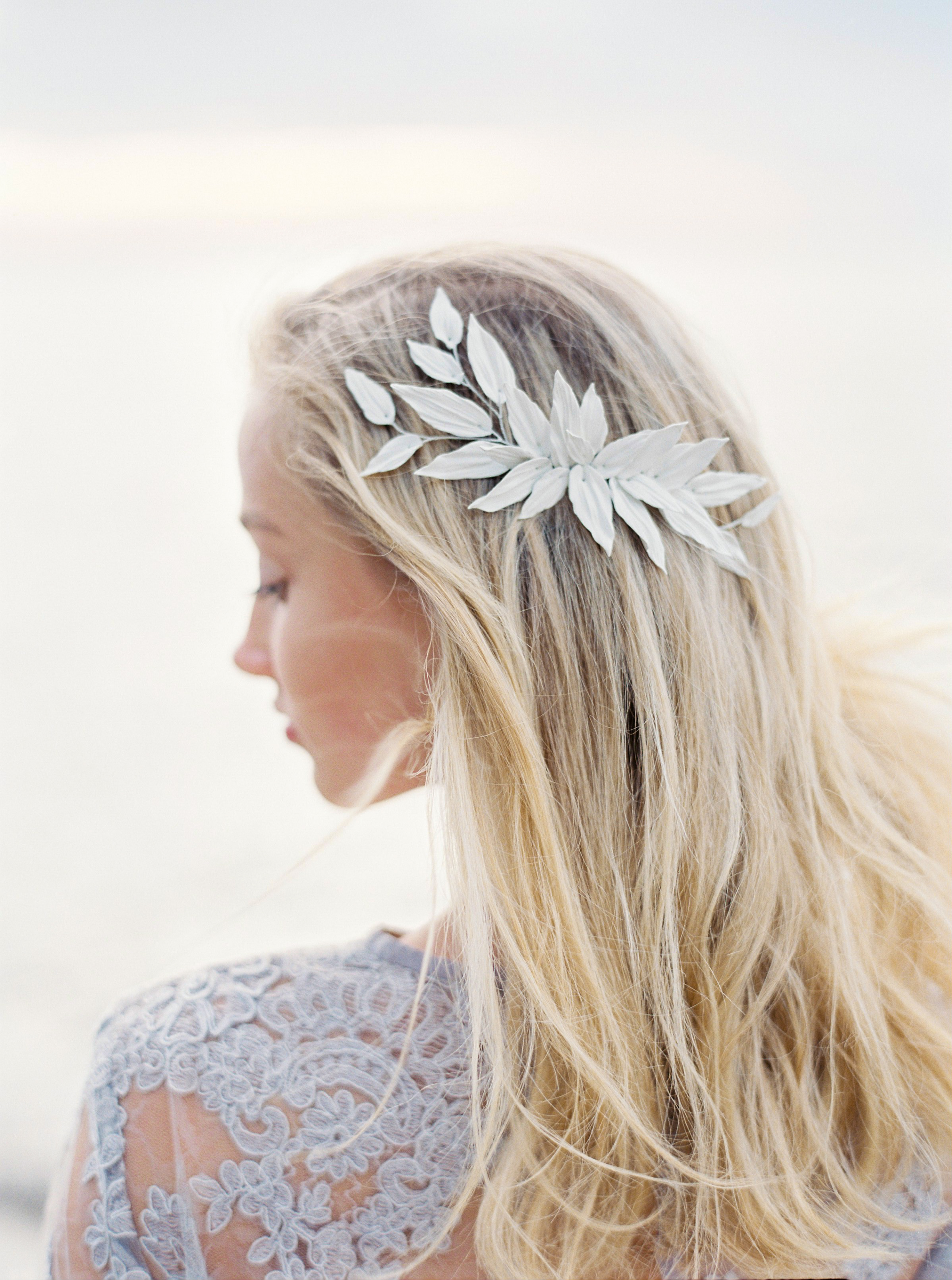 A hair comb with a collection of porcelain leaves was perfect for this beach bride, whose wedding was planned by Elins Art Studio. When you're selecting hair accessories for your big day, considering your destination will help ensure your bridal look feels cohesive with the locale.