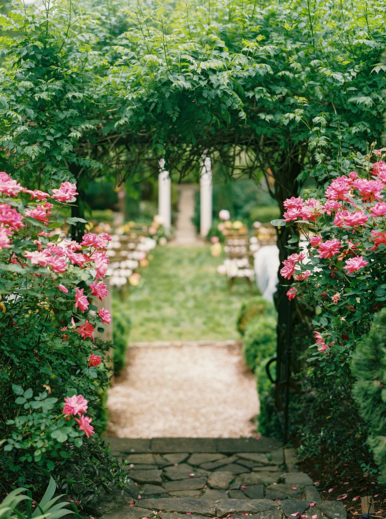 ashley scott wedding ceremony stone entrance to garden pink flowers
