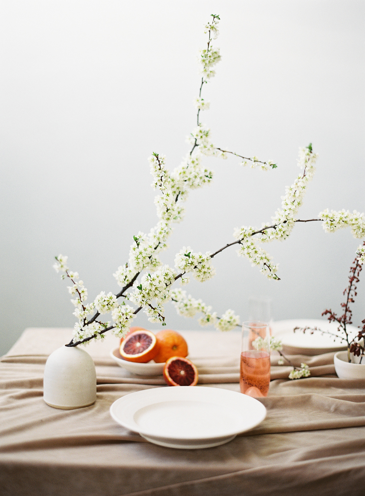 minimalist ikebana short vase with tall flowers on table with oranges