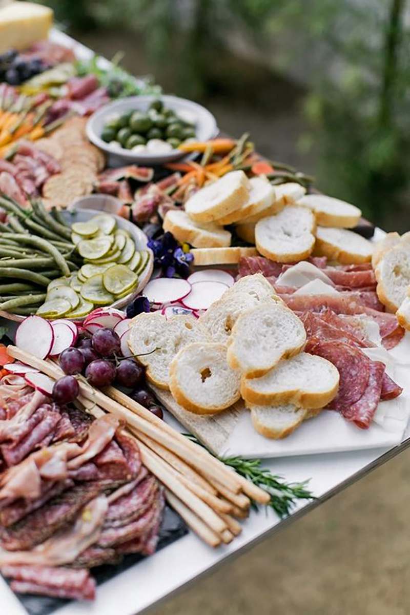 wedding grazing table with crostini, breadsticks, salami, veggies, and olives