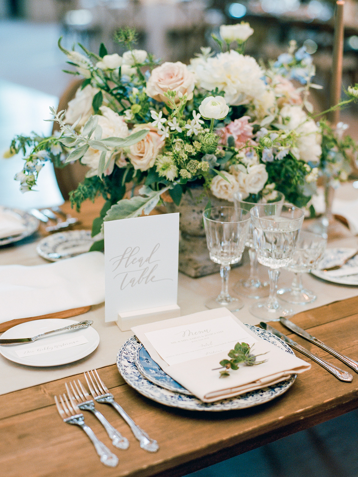 jessica aaron wedding place setting blue ornate dishes and floral arrangement