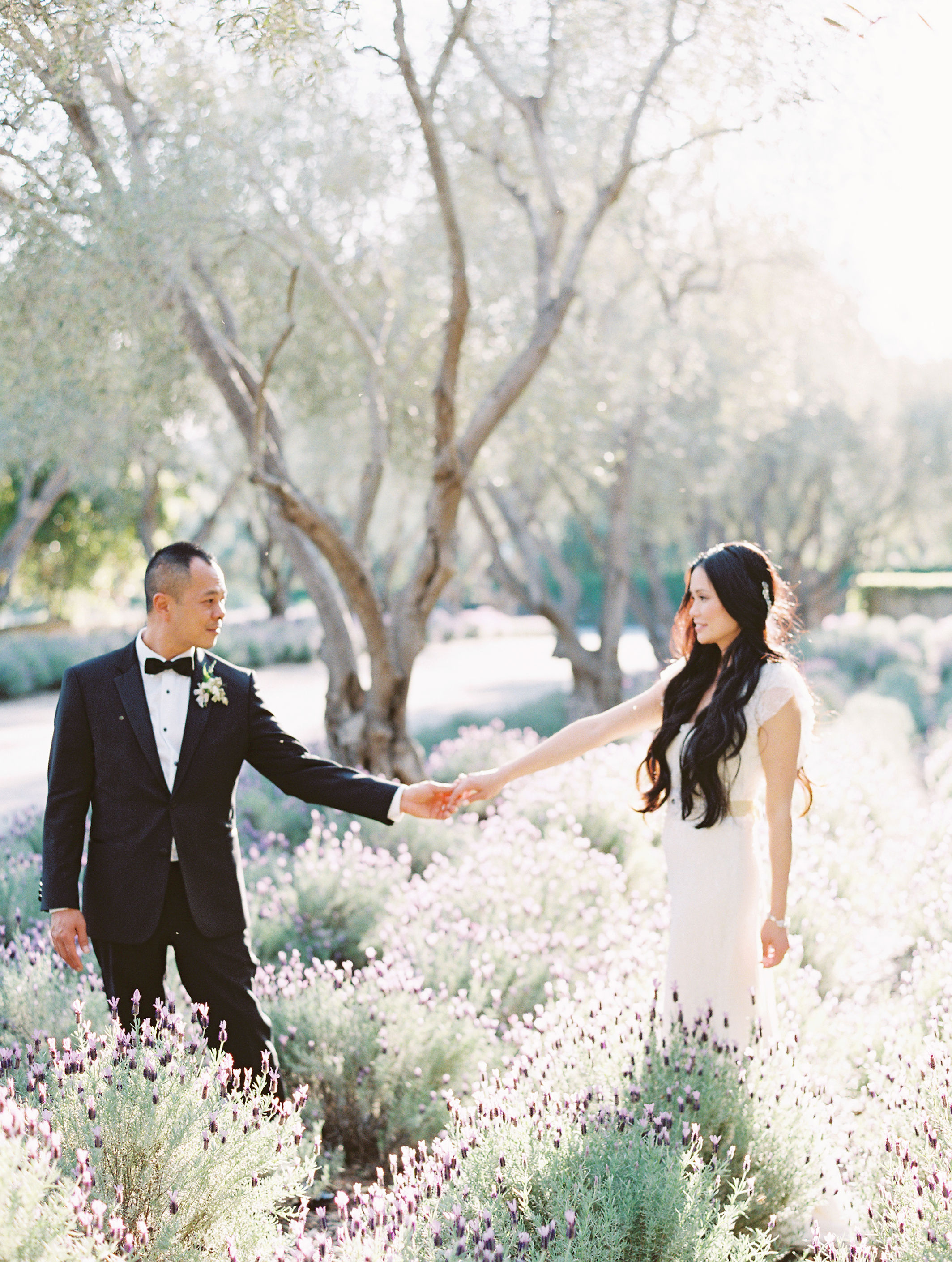 bride and groom holding hands in field of flowers