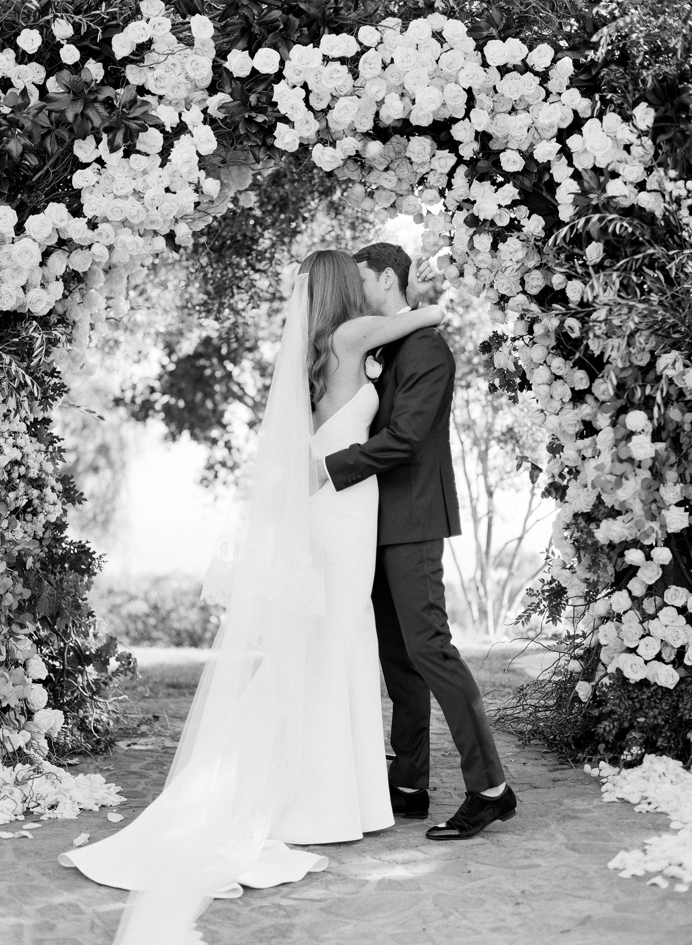 Gloria and Jordan kissing under arch black and white