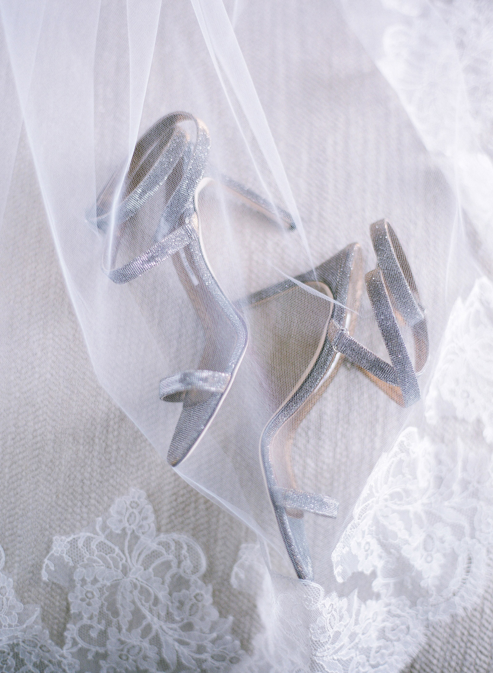 silver wedding shoes beneath veil