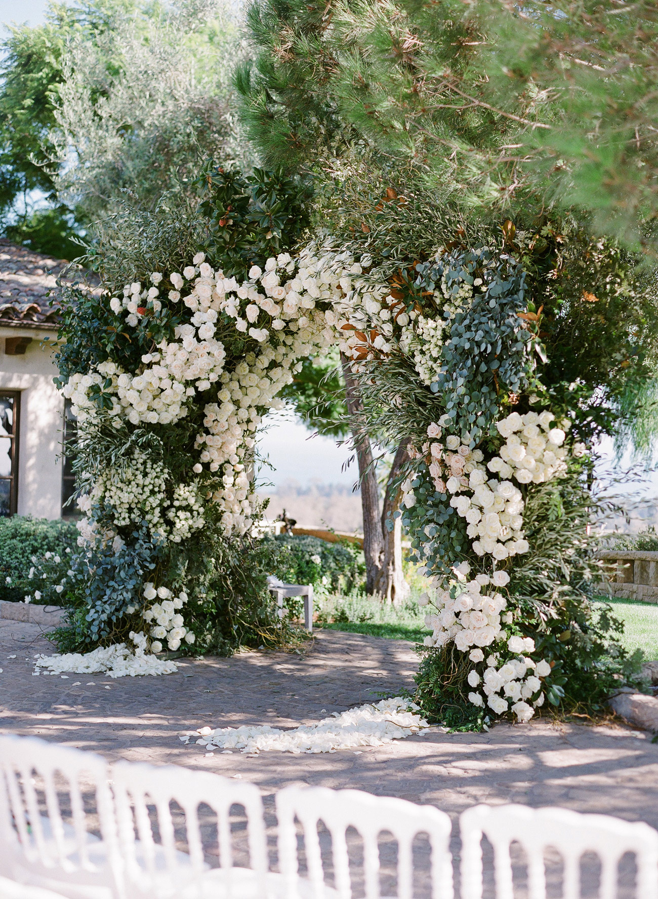 close-up wedding arch decorated with greenery white roses