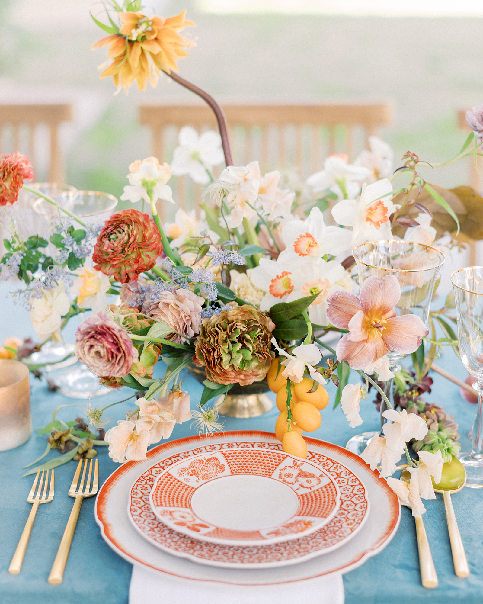 Planning a wedding over the Fourth of July weekend? Reinterpret the holiday's signature red, white, and blue color scheme in a newfangled way for your rehearsal dinner (this is particularly fun if your wedding has a completely different palette). A dusty blue La Tavola tablecloth contrasted the vintage red-and-white patterned dinnerware on this Smith + James Events setup; an ultra-colorful centerpiece, which Kelly Lenard filled with orchids, mums, ranunculus, lilies, sweet peas, and kumquats subtly referenced the shades below.
