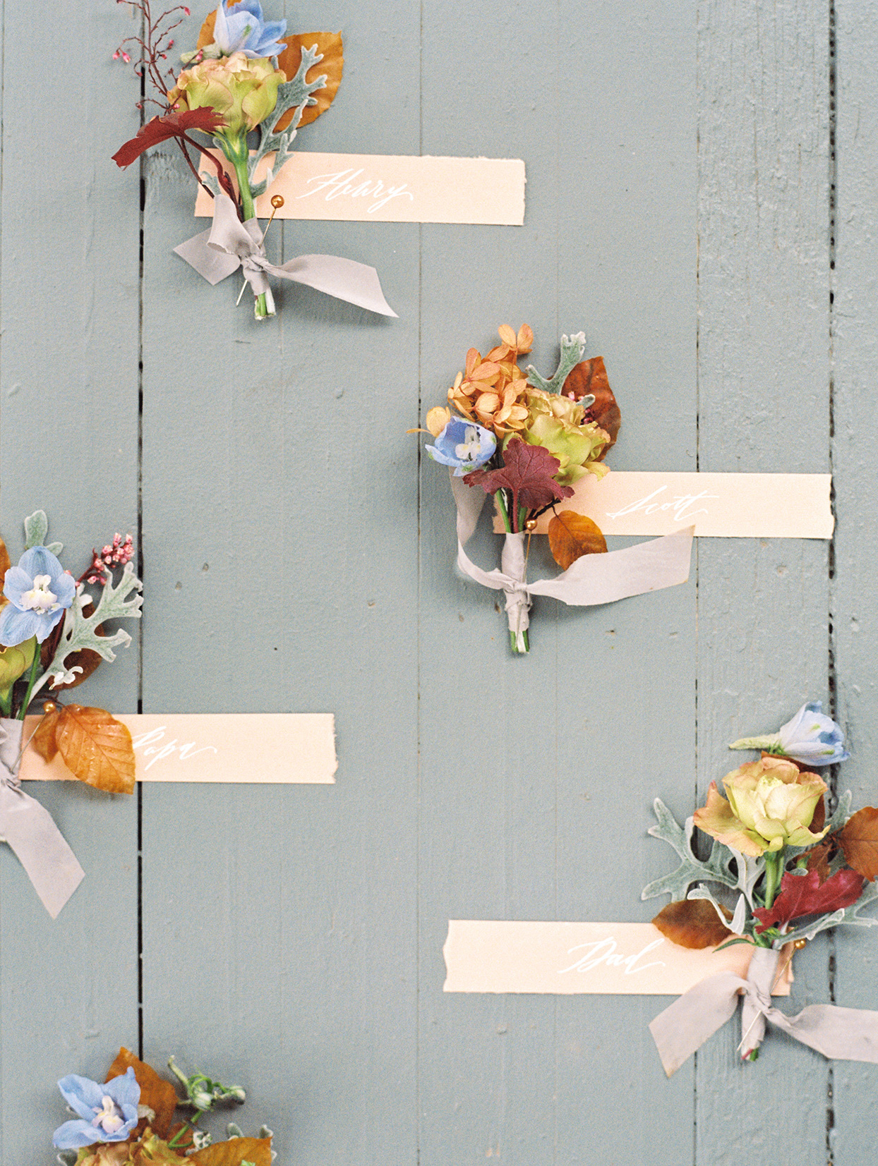 elizabeth scott wedding boutonnieres on painted wooden table