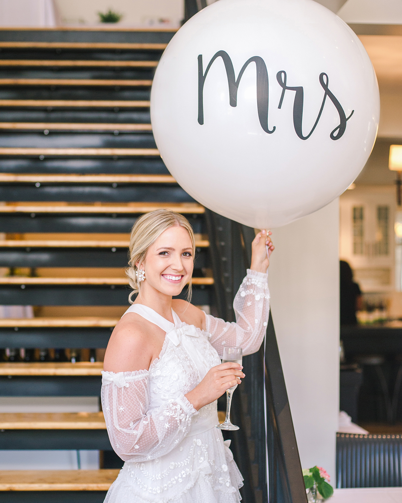 bride holding large mrs balloon
