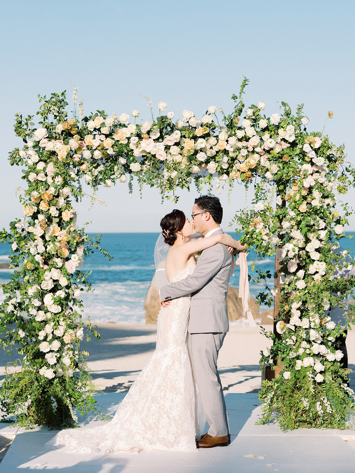 kirsten deran wedding ceremony kiss in front of floral arch