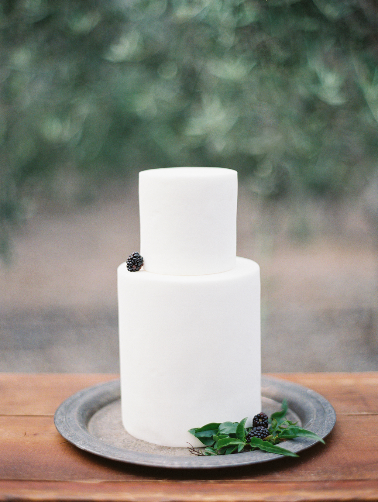 tall white wedding cake with simple blackberries