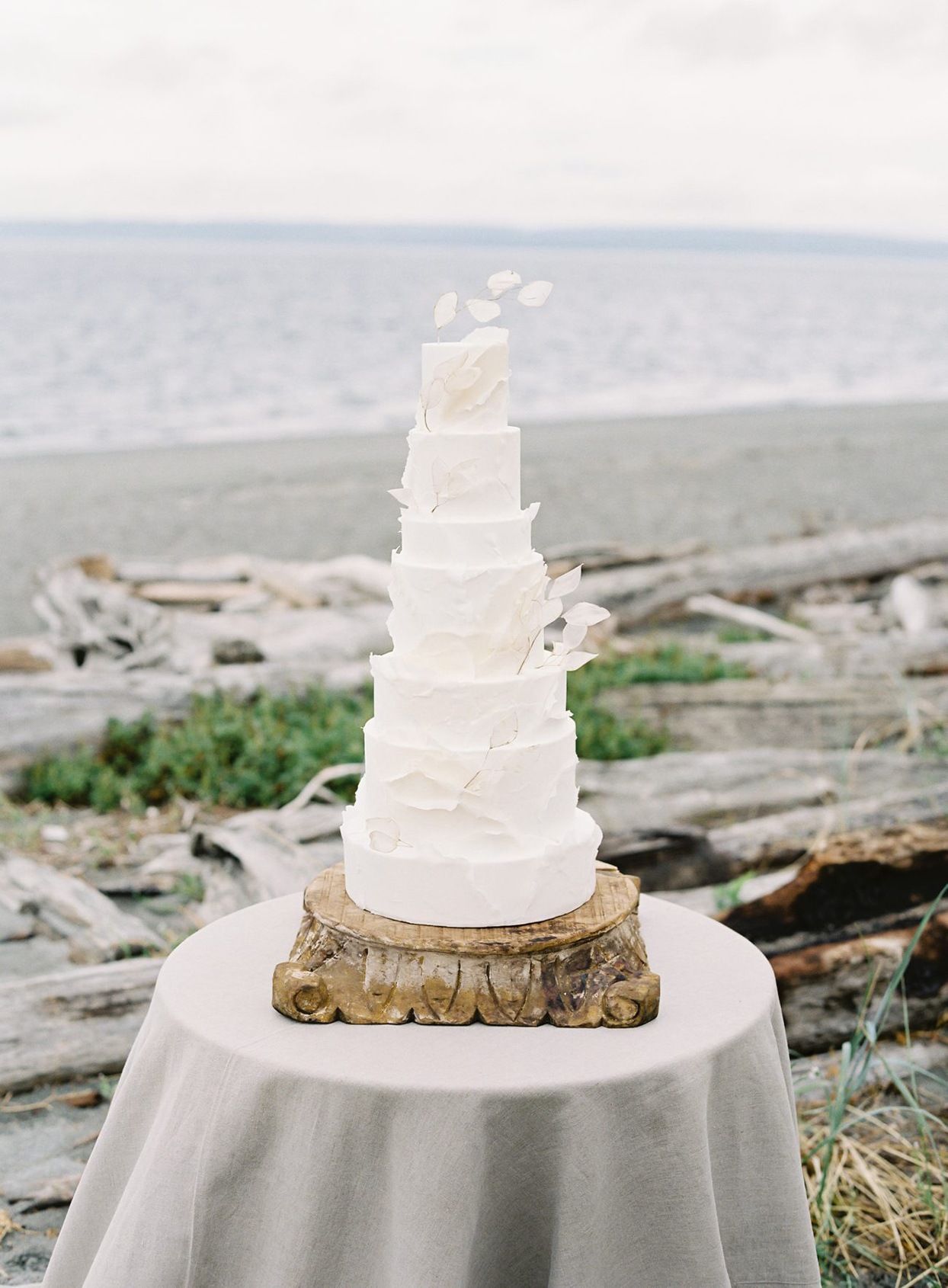 white wedding cake with fondant waves by ocean