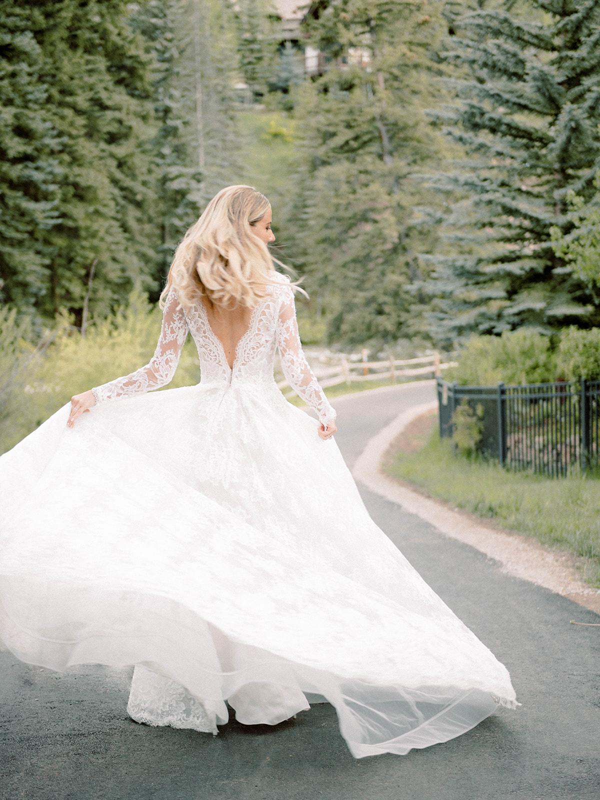 bride walking down wooded path wedding dress