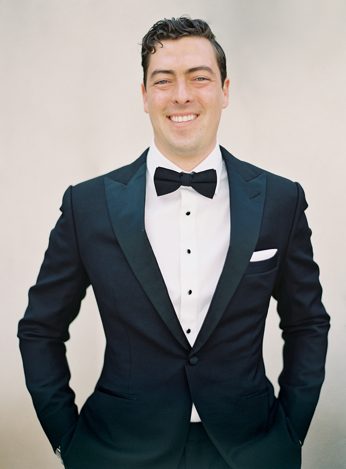 groom posing bespoke black suit