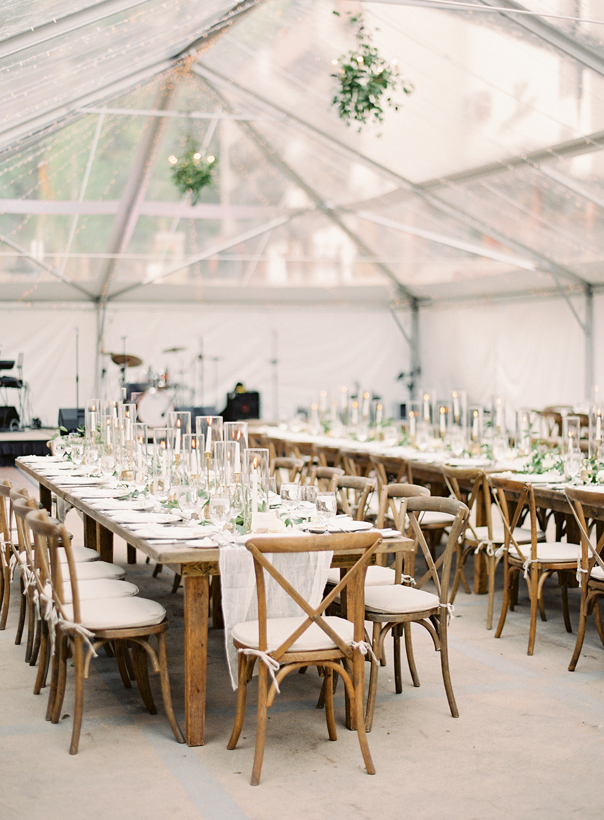 wedding reception tent greenery plus wooden tables