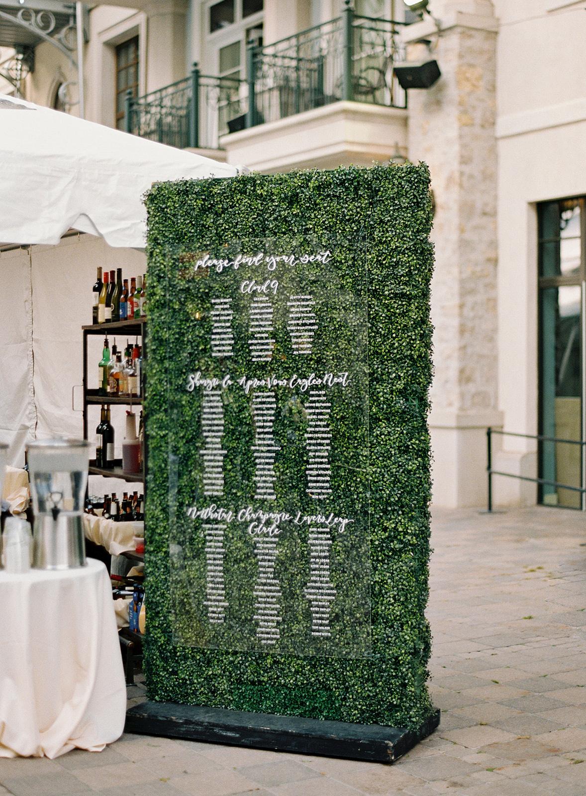acryllic board seating chart greenery wall