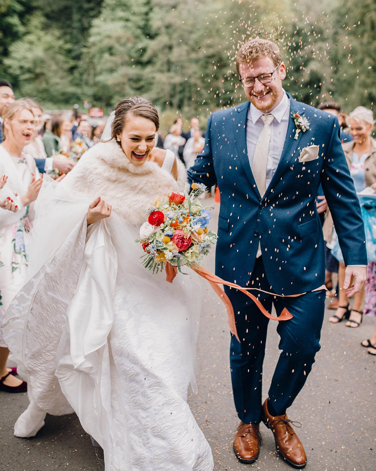 bride groom walk as guests throw confetti