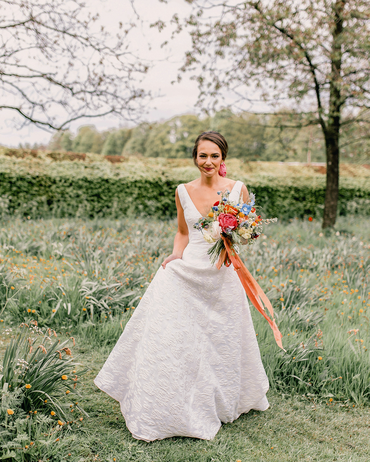bride in dress walking through grass with floral bouquet