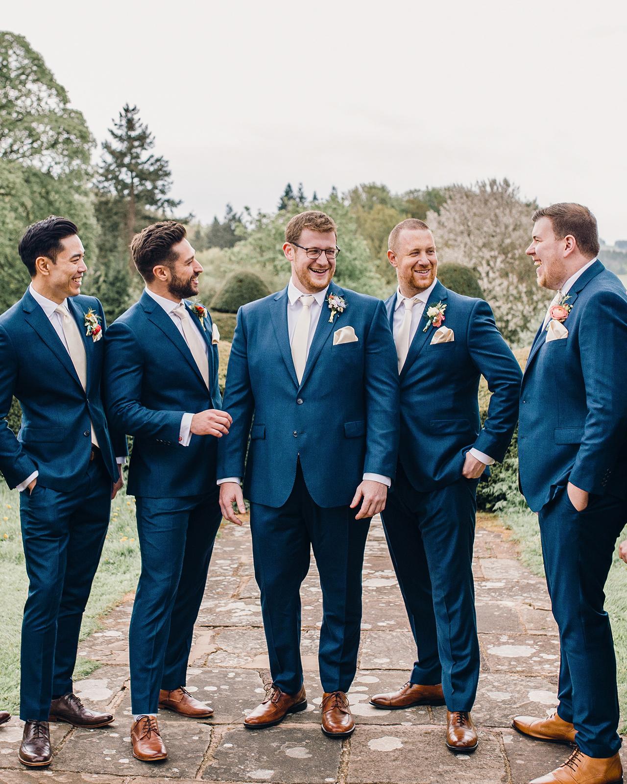 groom with groomsmen in navy blue attire outdoors