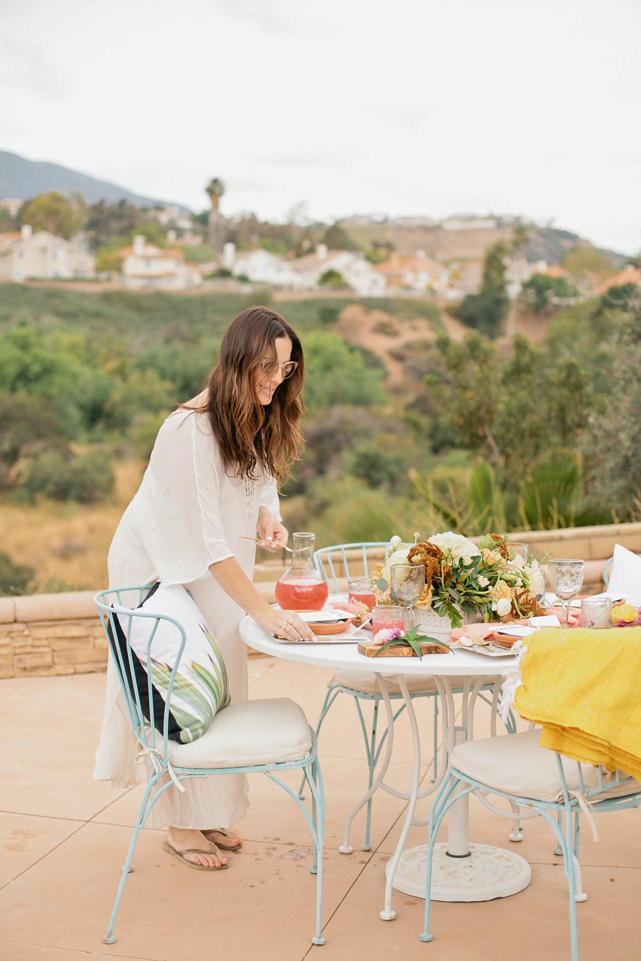 woman setting table mountain view terrace