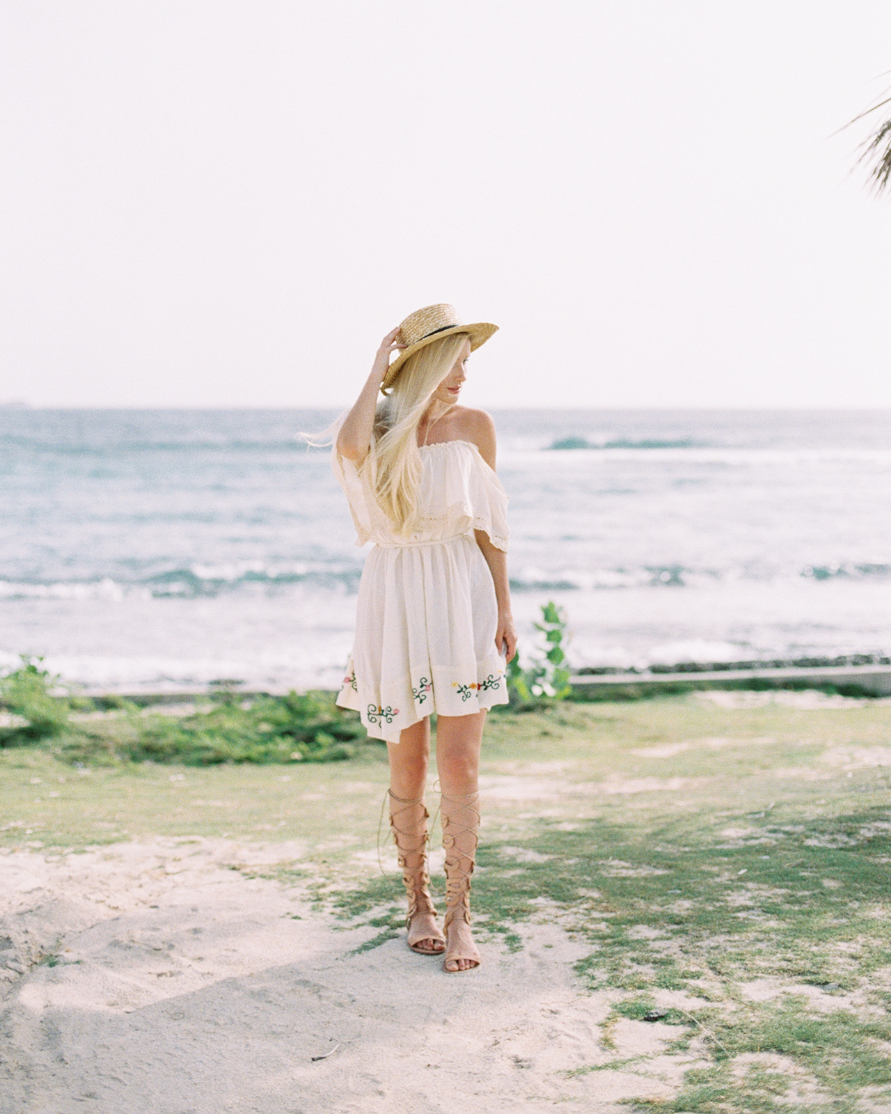 woman walking on beach in white dress with hat