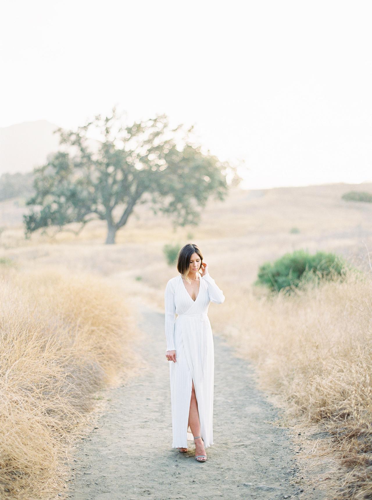 woman walking down sand bath long white v-neck dress