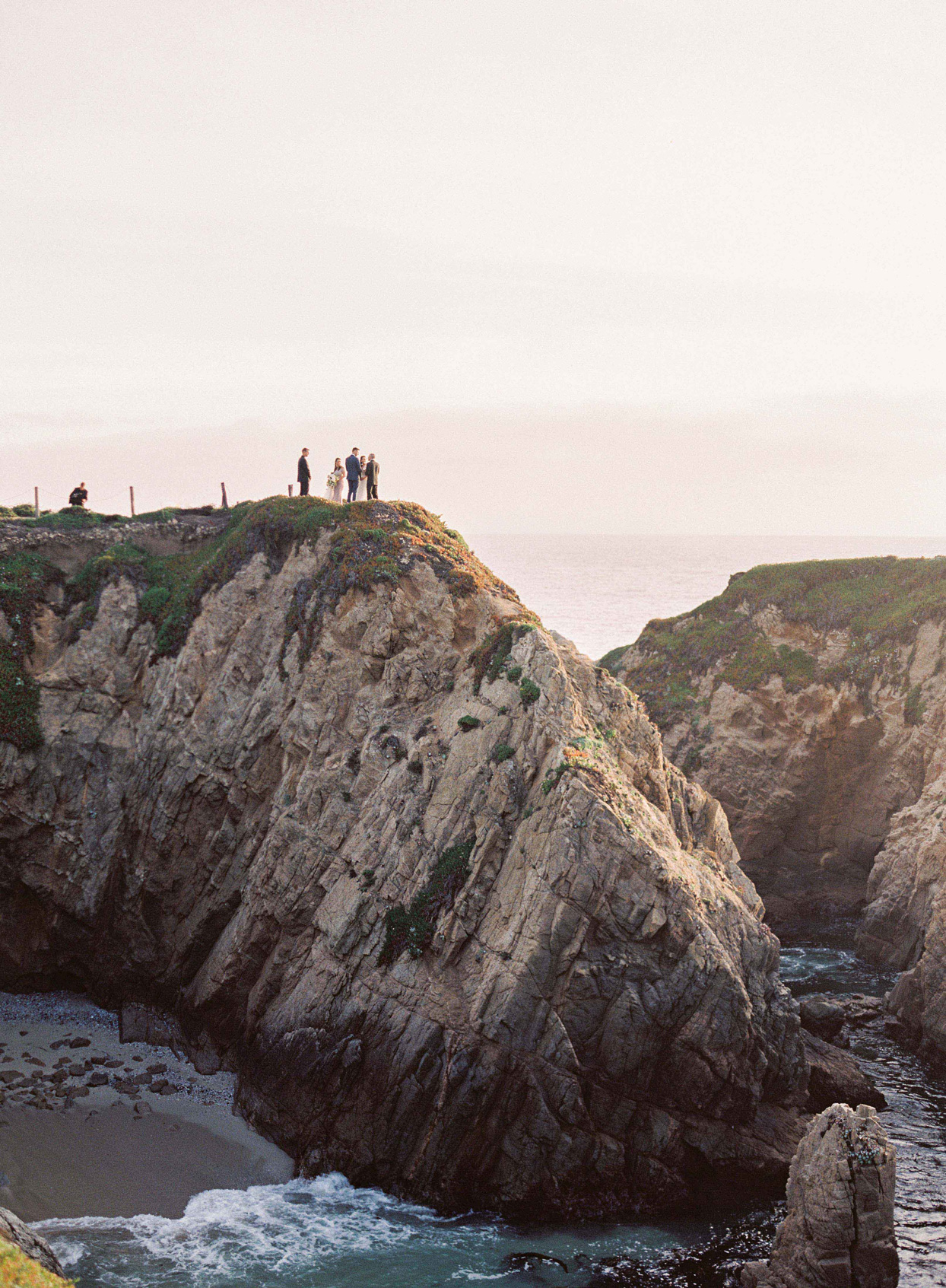 wedding party standing on cliff by the ocean