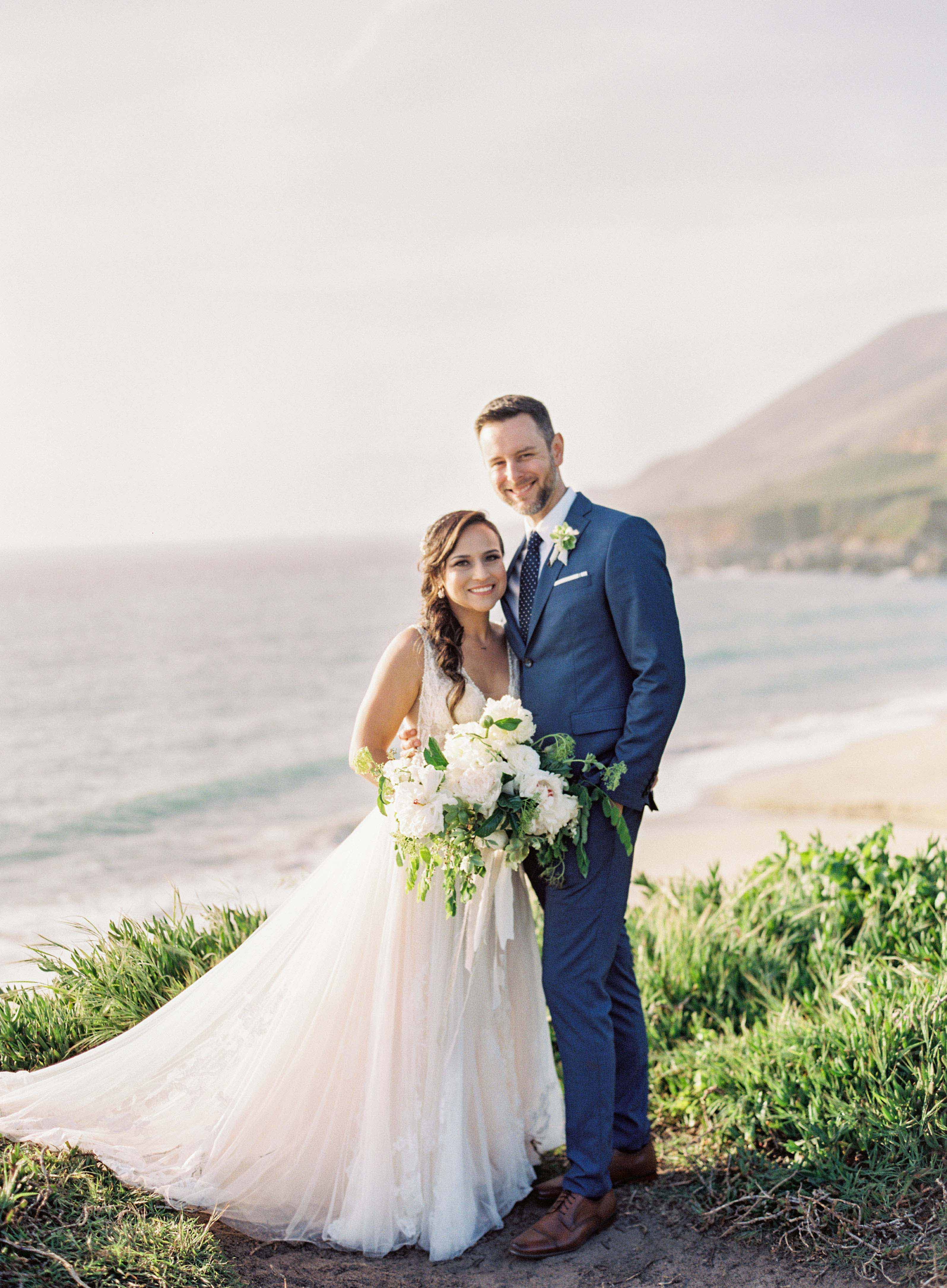 bride and groom smile on cliff by the ocean