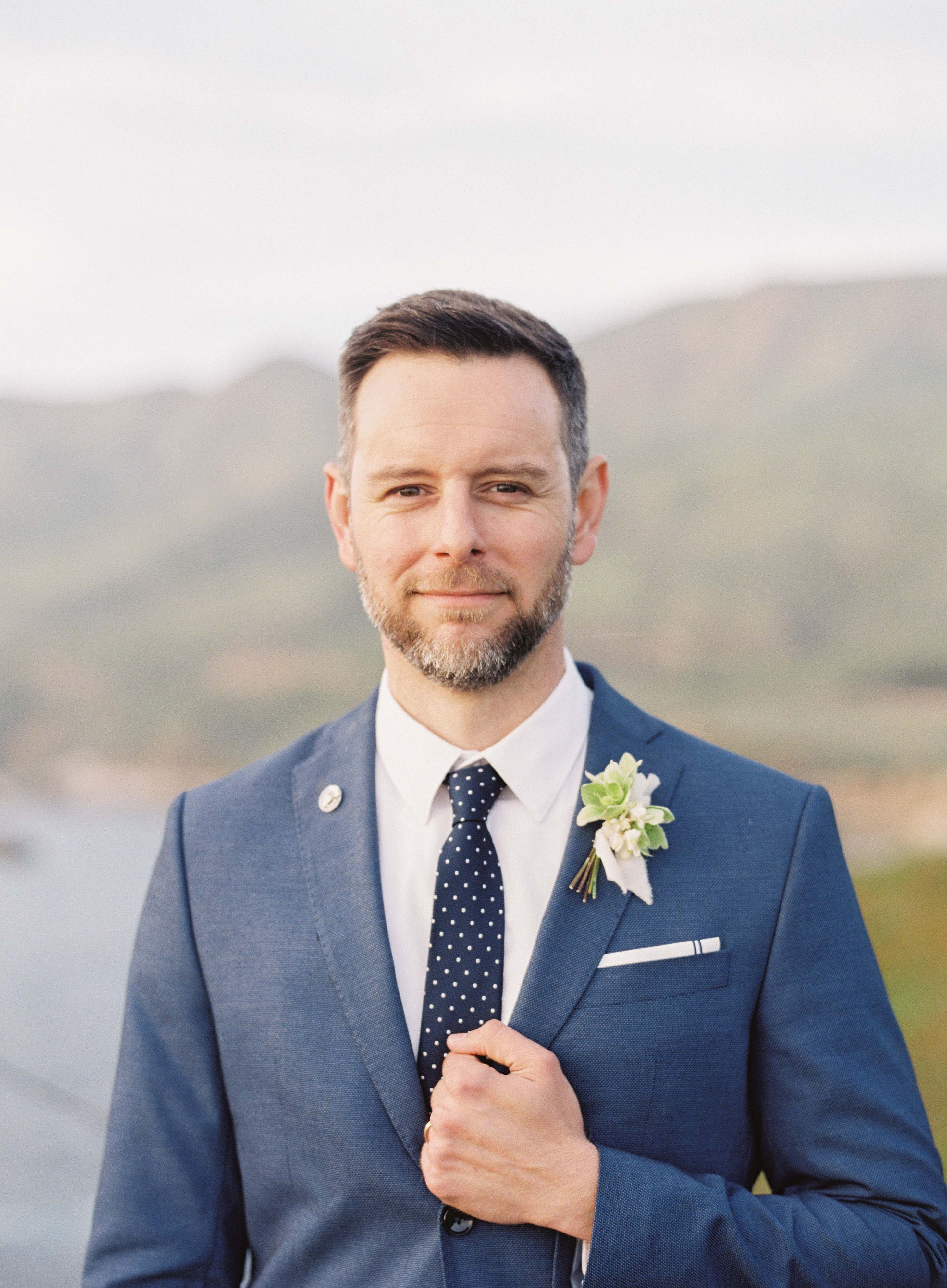 groom wearing navy blue suit and tie with polkadots