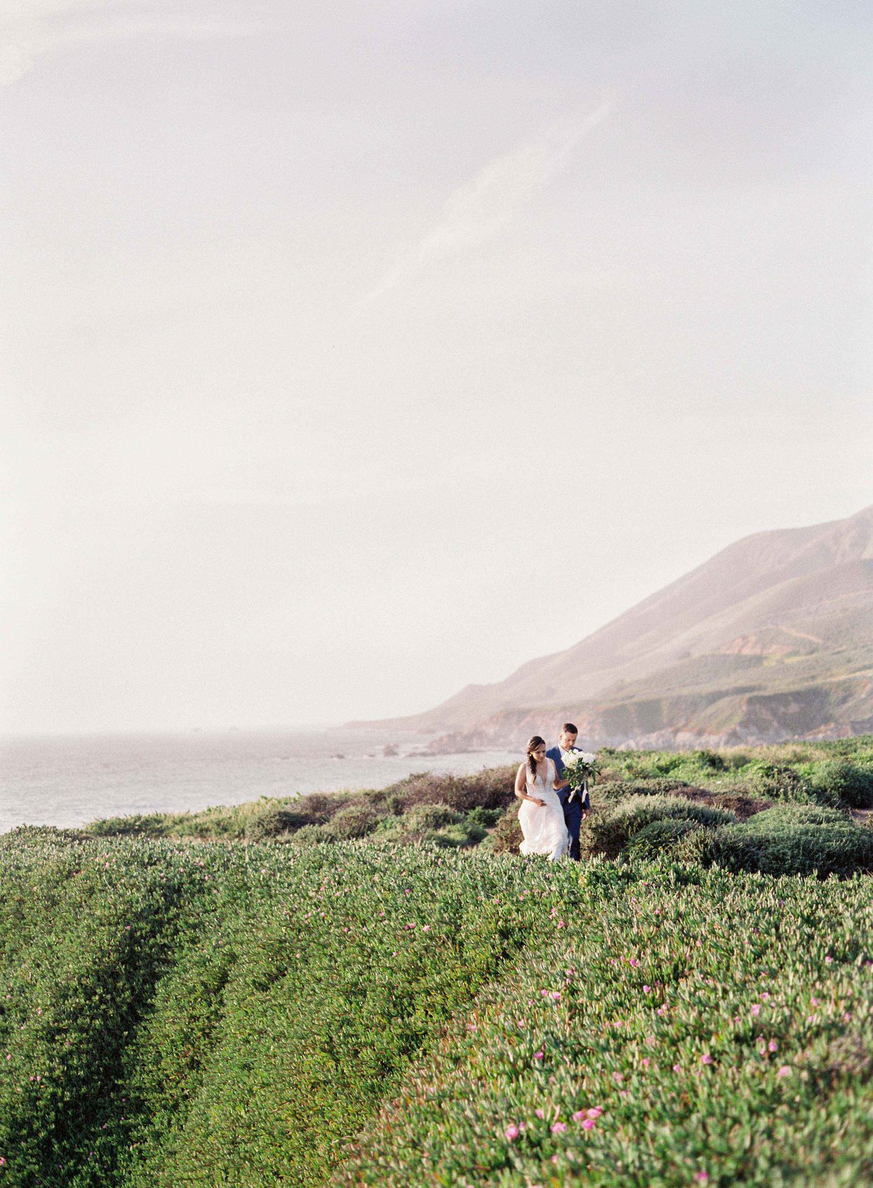 bride and groom walk through green field on cliff side