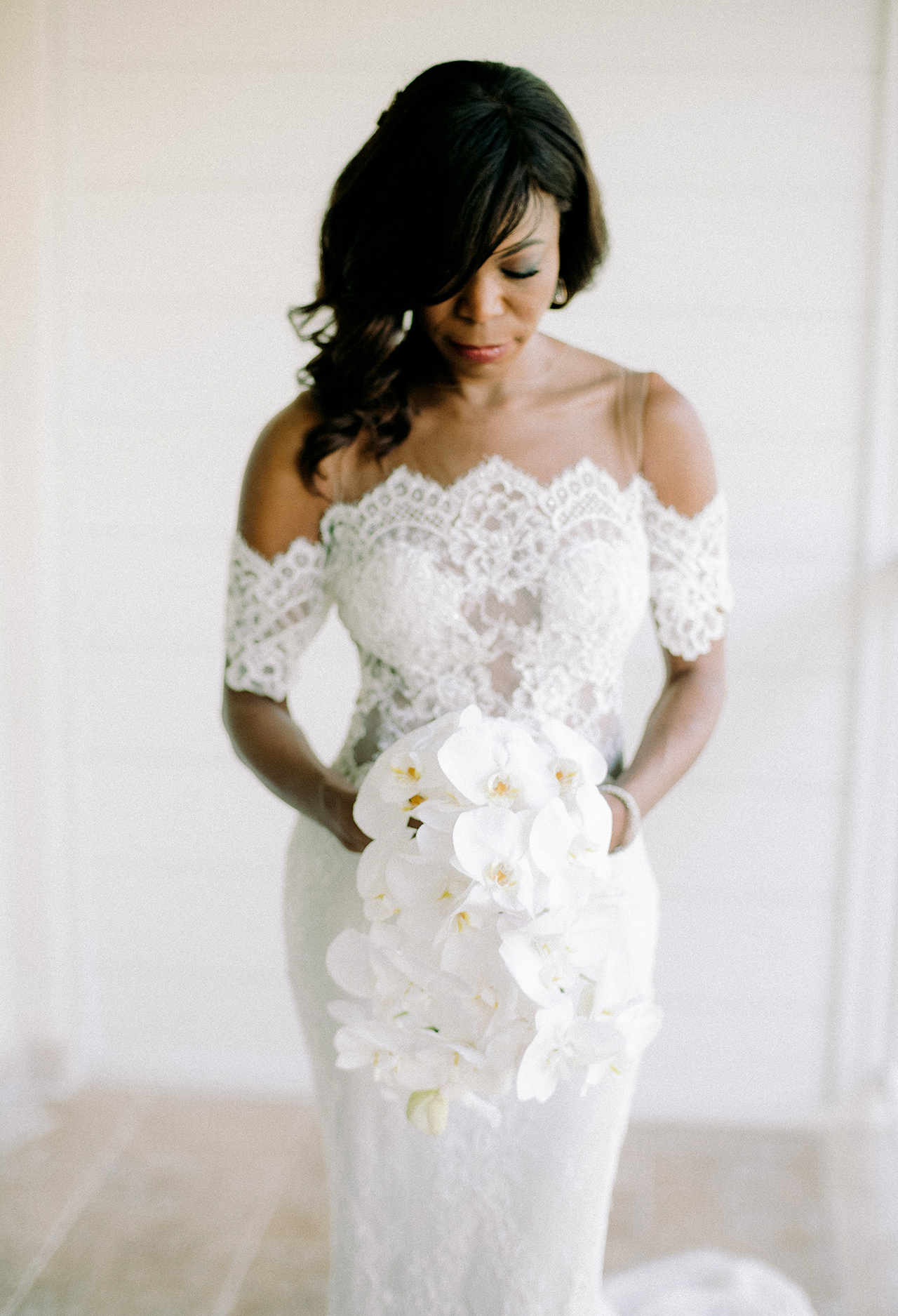 bride holding bouquet of white orchids
