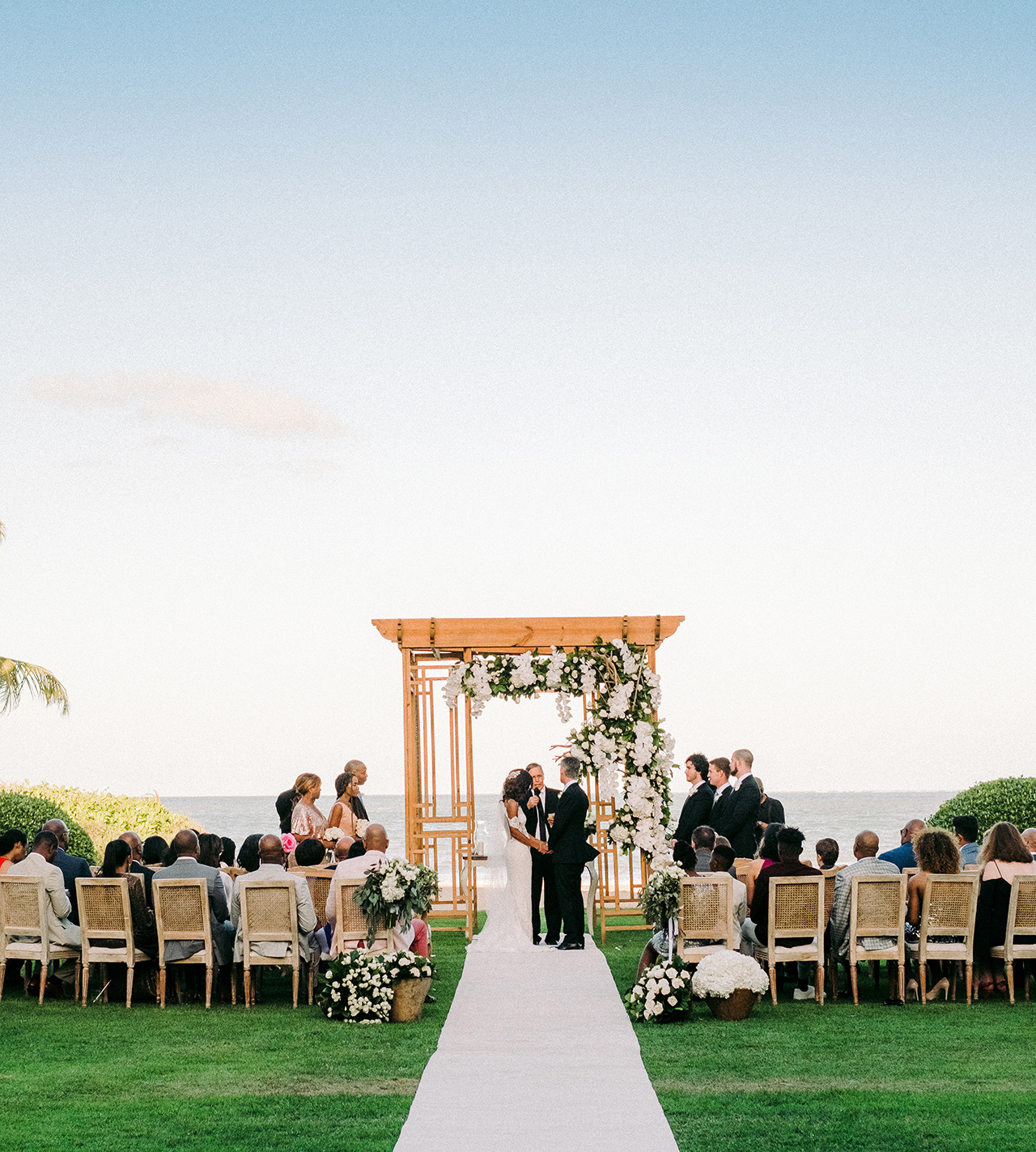 wedding ceremony outdoor ocean view white floral arrangements