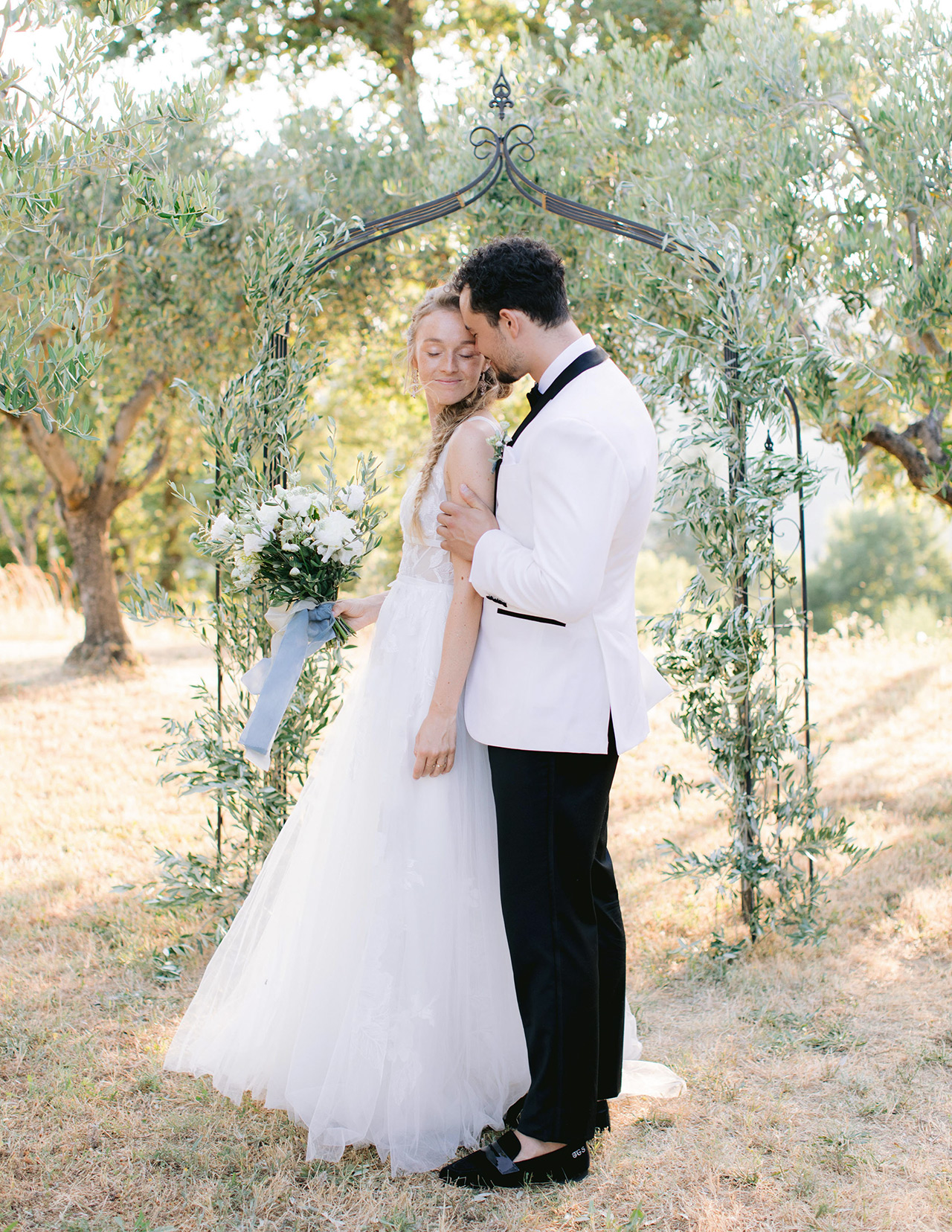 bride groom pose olive branch wedding arch