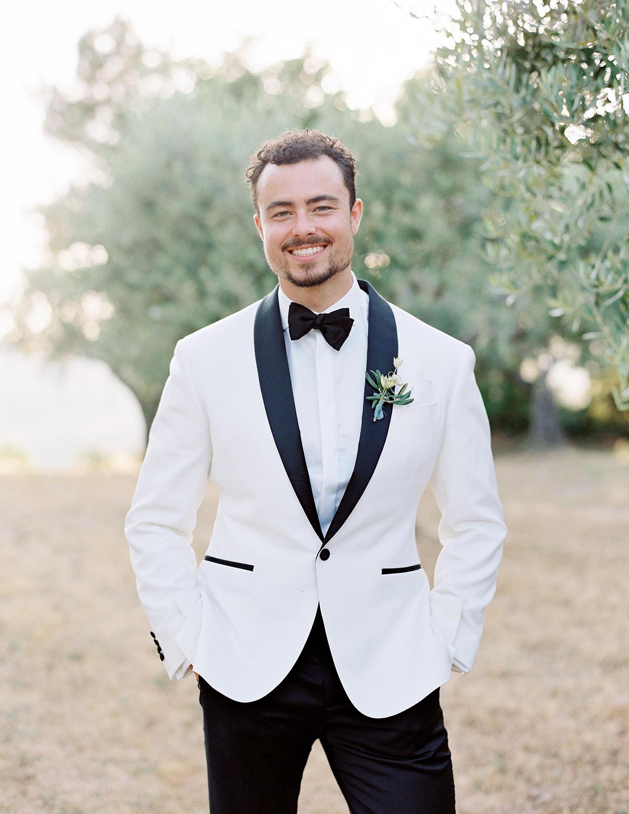 groom posing in white jacket tuxedo