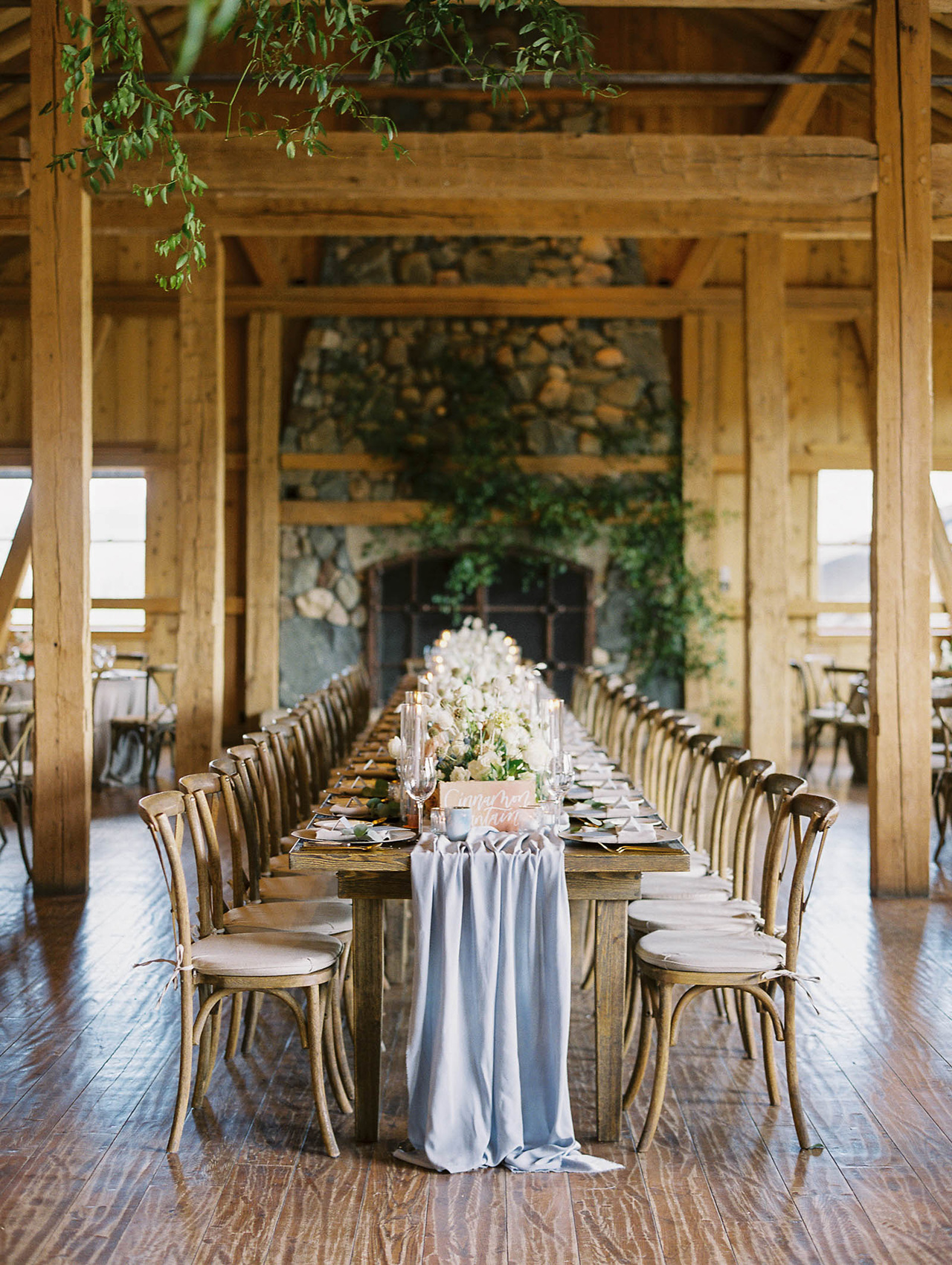 long wooden table blue silk runner reception