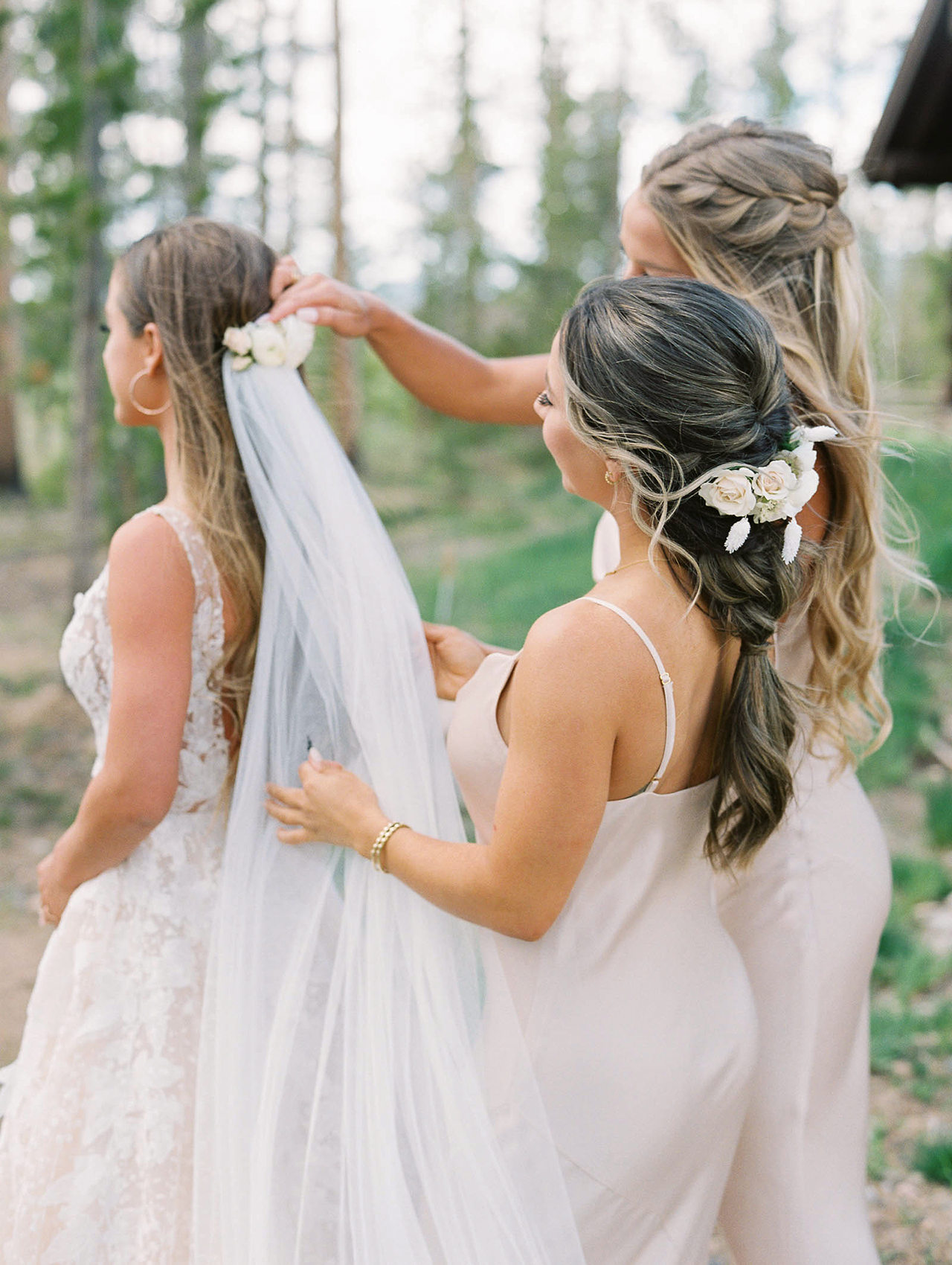 bridesmaids placing brides vail outdoors