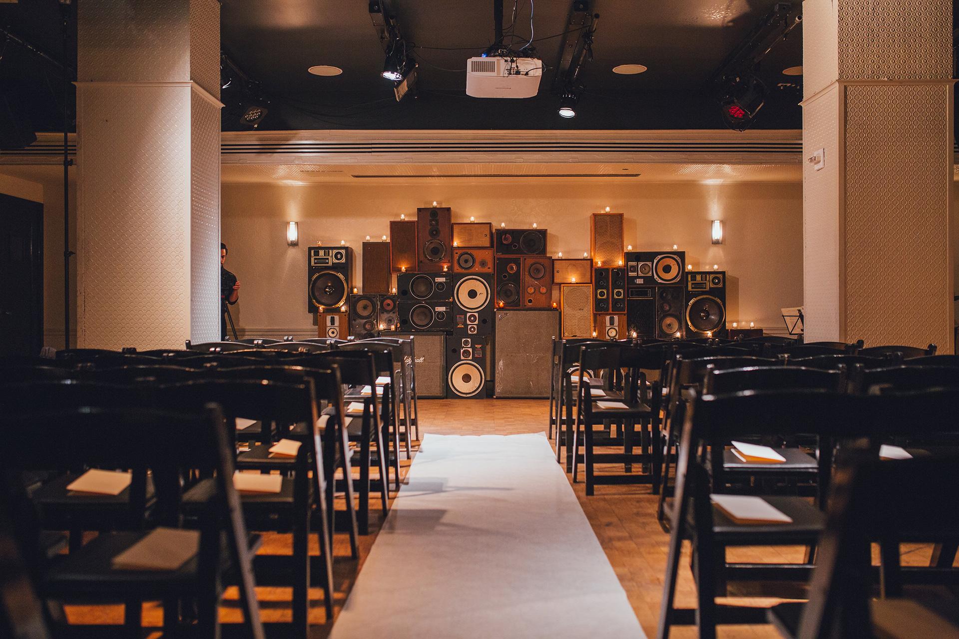 wedding venue black folding chairs speaker display